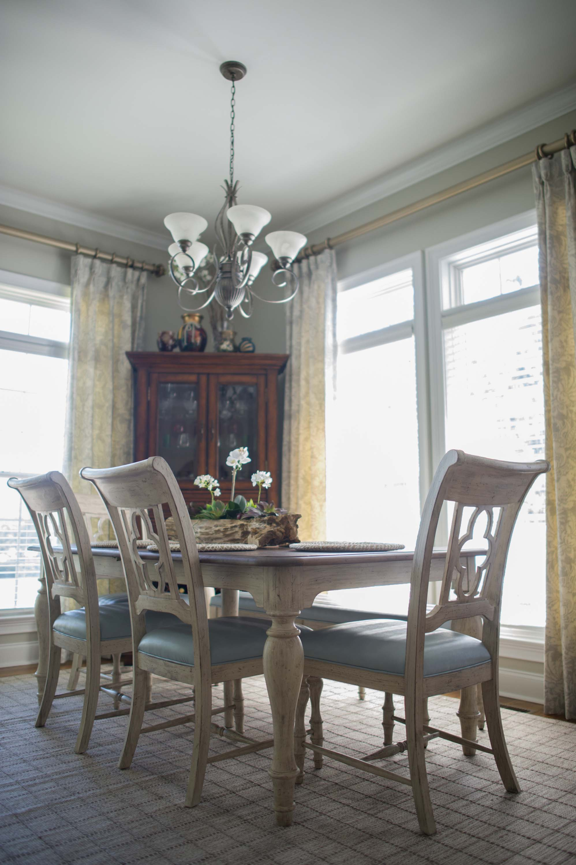 Dining room with wooden table, chair with soft seat and chandelier