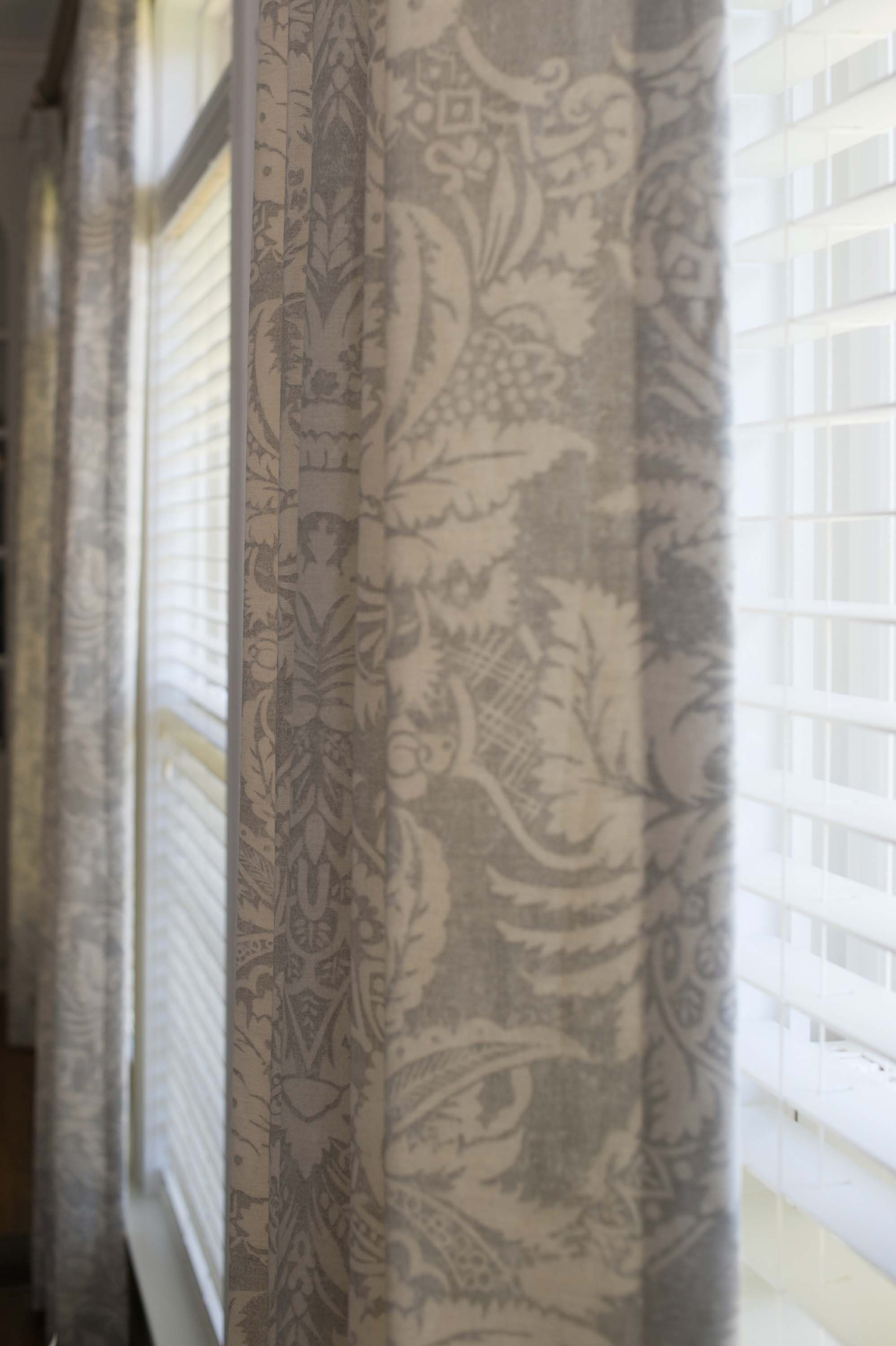 Window with horizontal window blinds and printed curtain