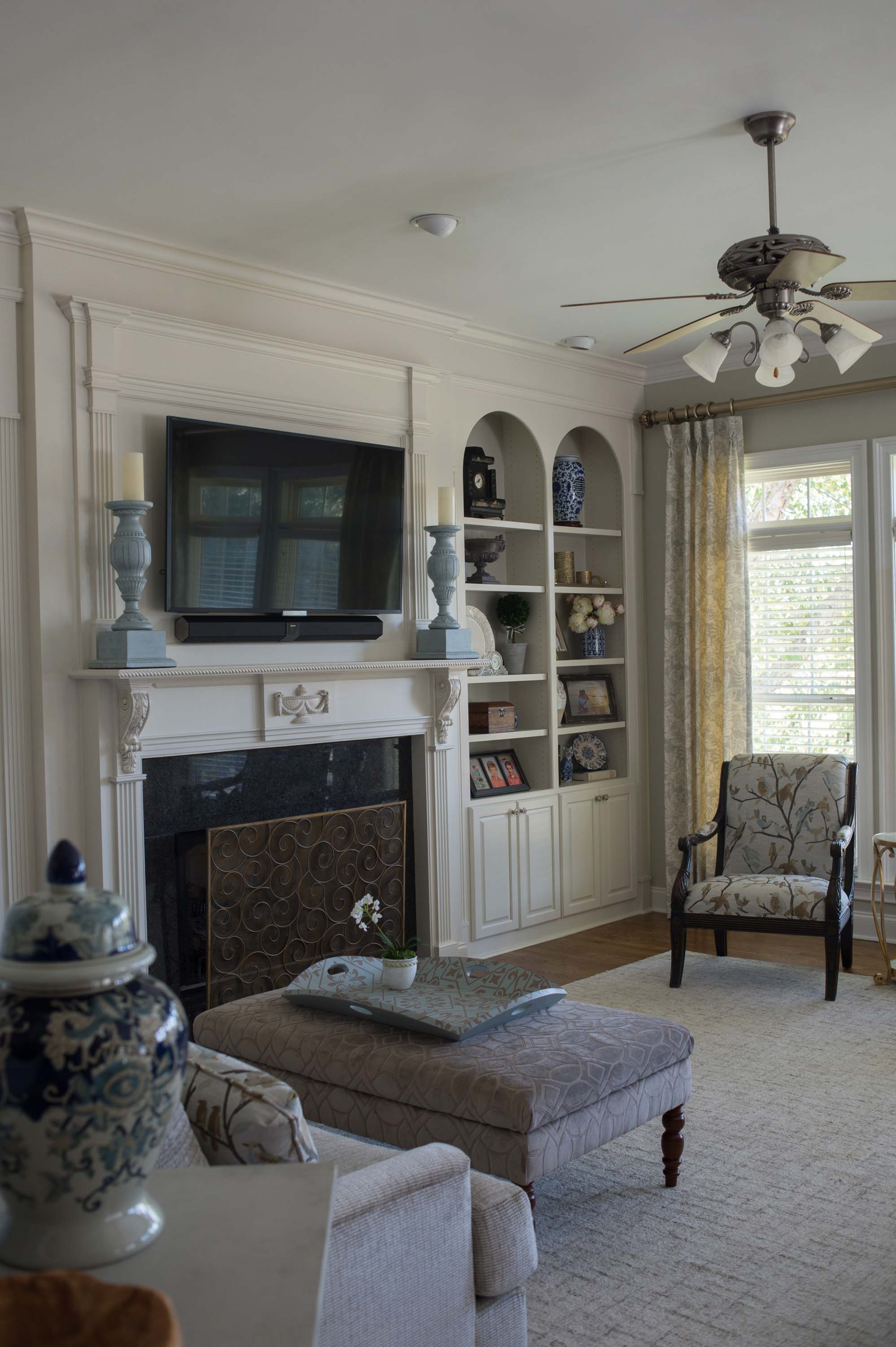 Living room with fireplace, ceiling fan and built-in cabinet
