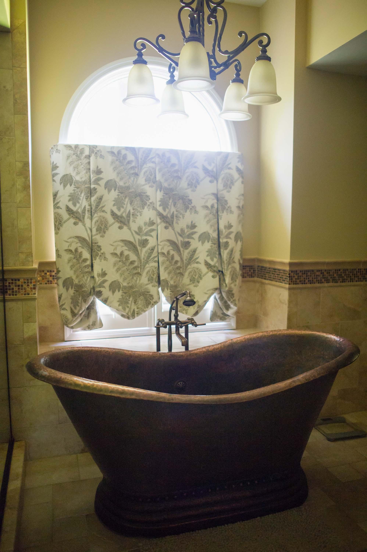 Bathroom with vintage bathtub, ceramic floor and chandelier