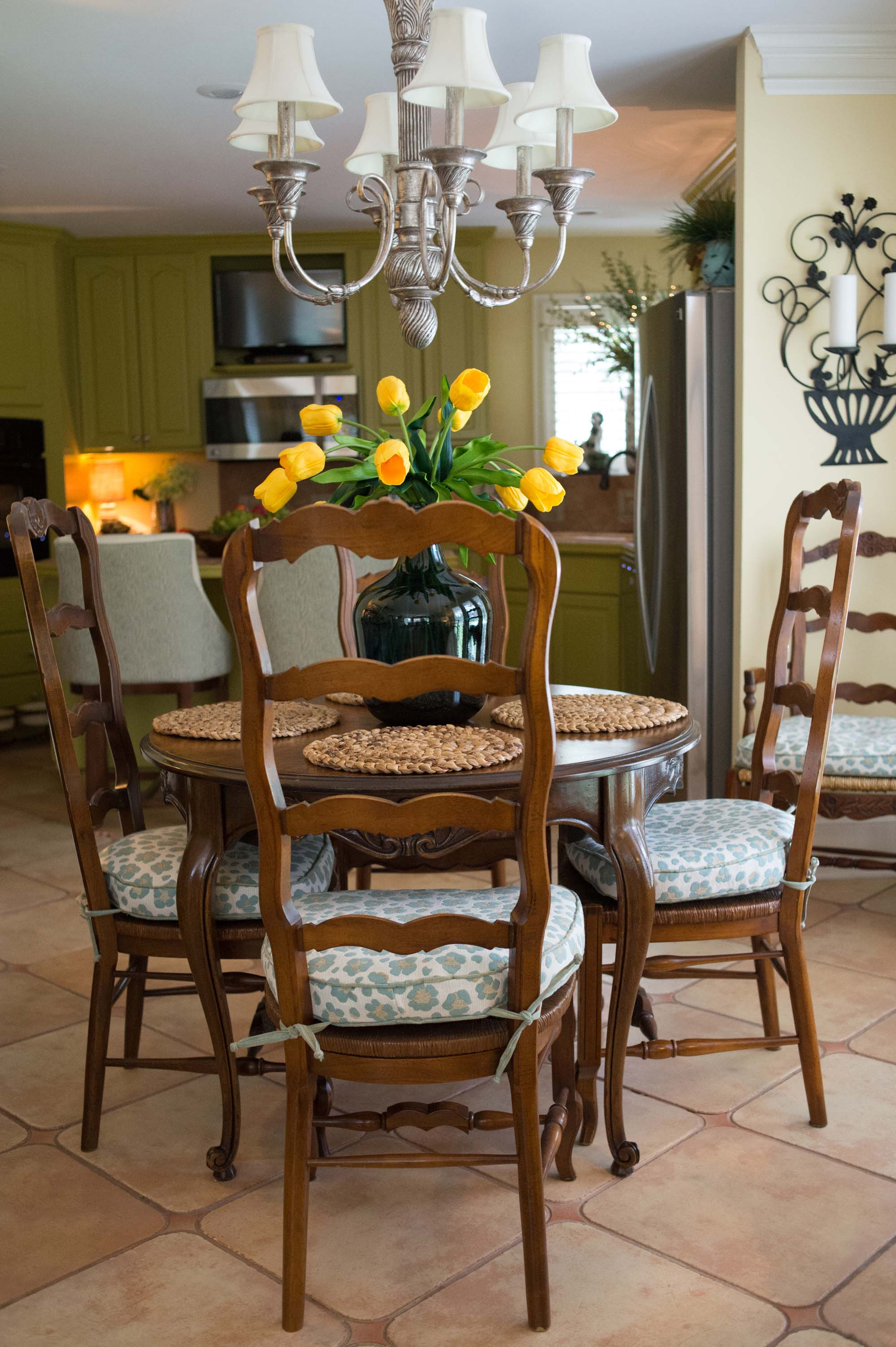 House interior with flower on round dining table, wooden chairs and chandelier