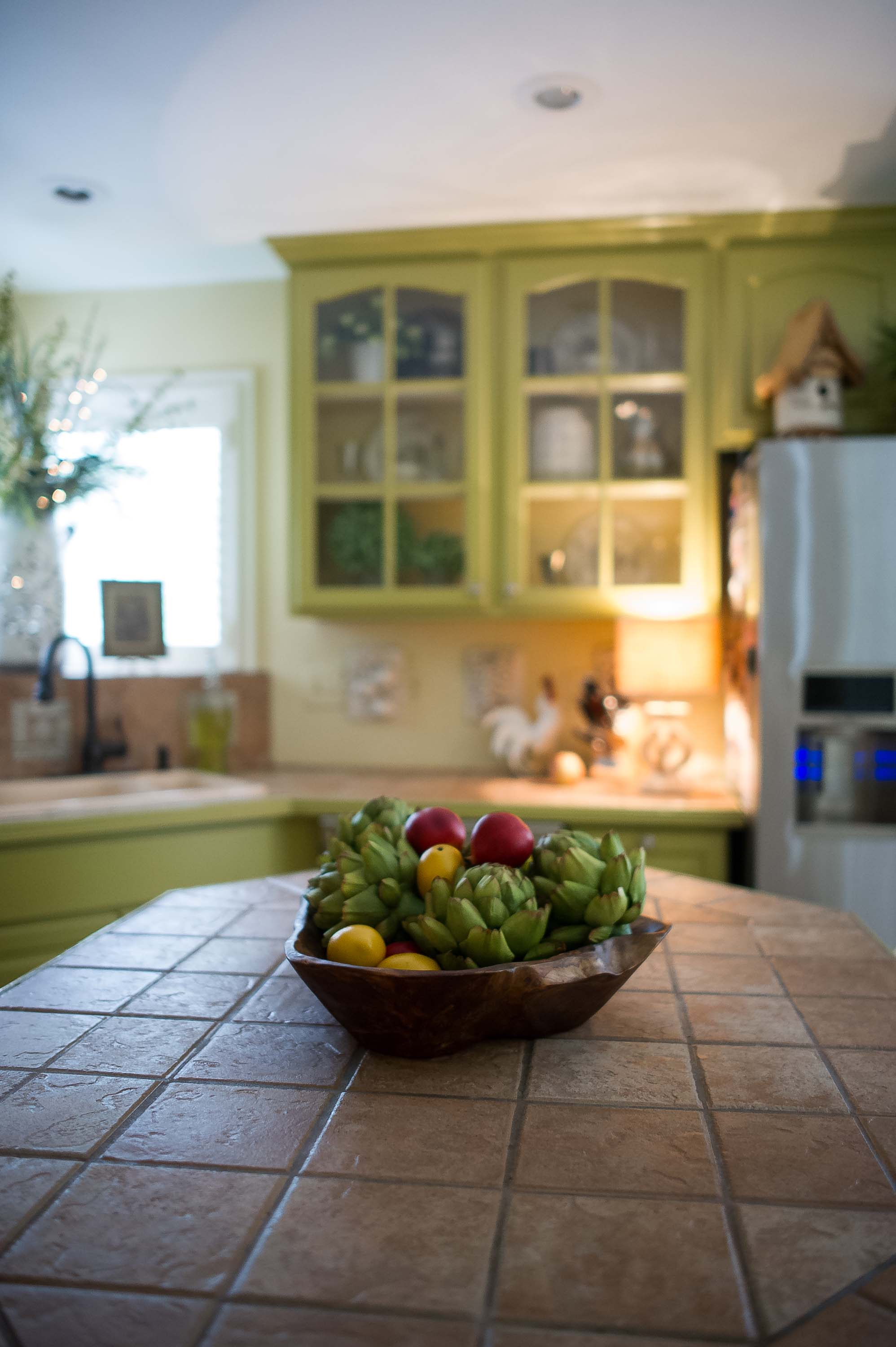 Kitchen with wooden fruit bowl on a ceramic tile countertop