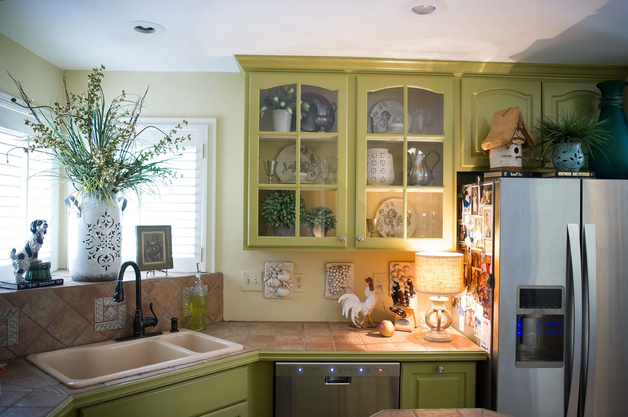 Kitchen with sink, ceramic tile countertop, wooden cabinet and  fridge