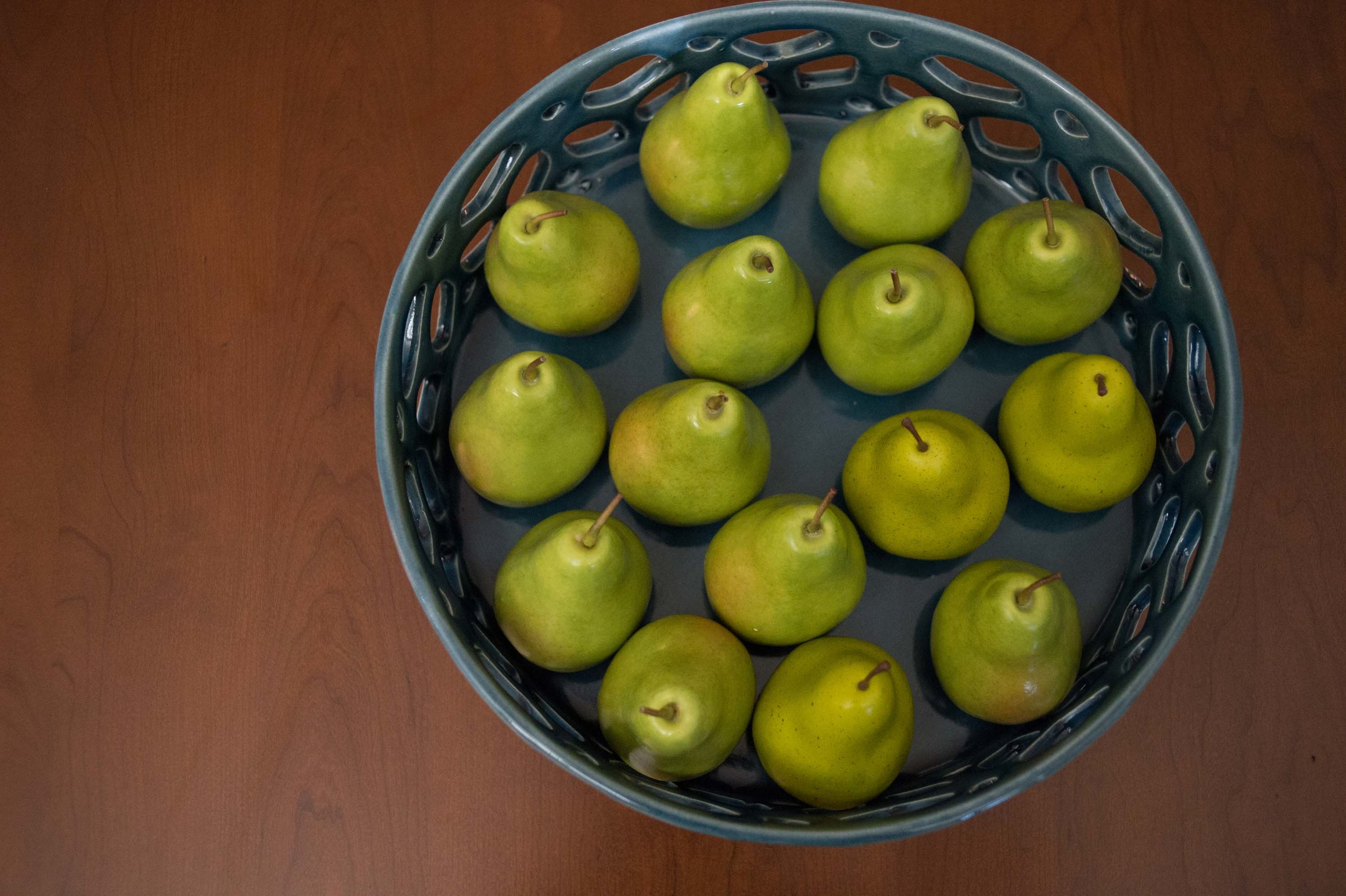 Pears on a ceramic modern style plate with wooden background