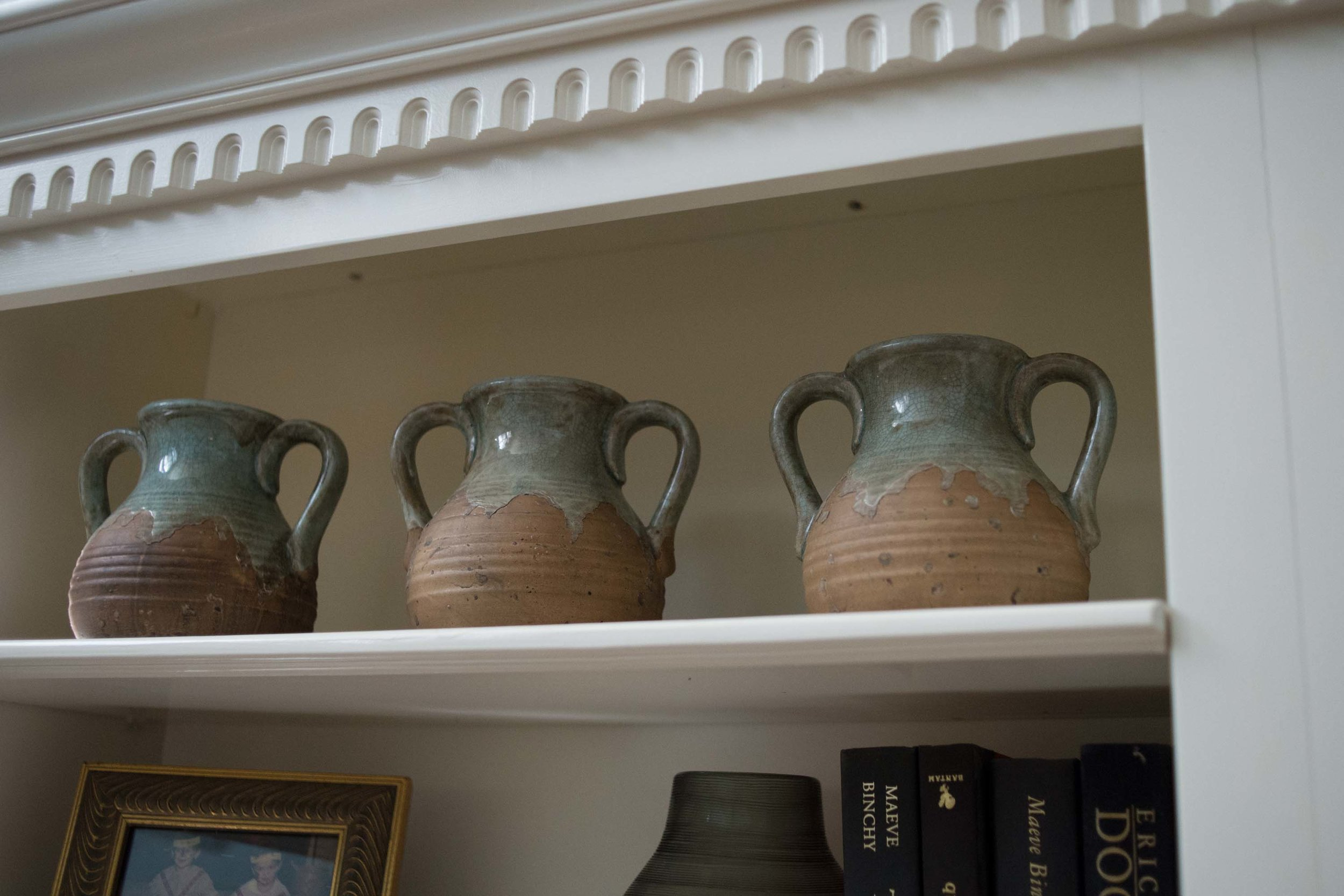 Shelves with books, vintage vases and picture frame