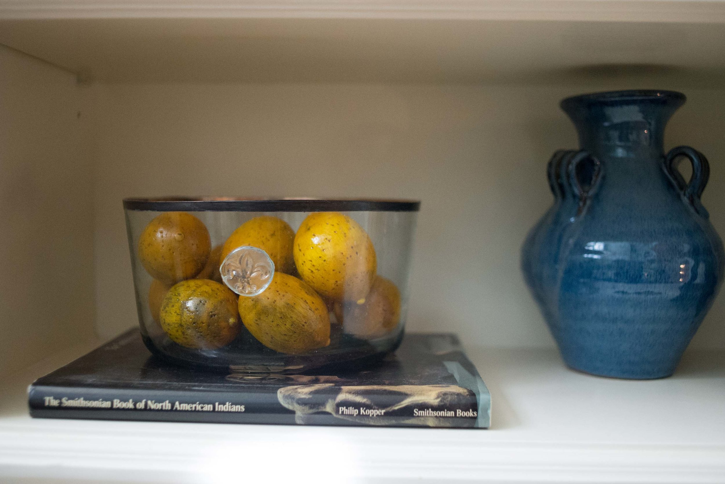 Shelf with bowl of fruits, book and ceramic vase