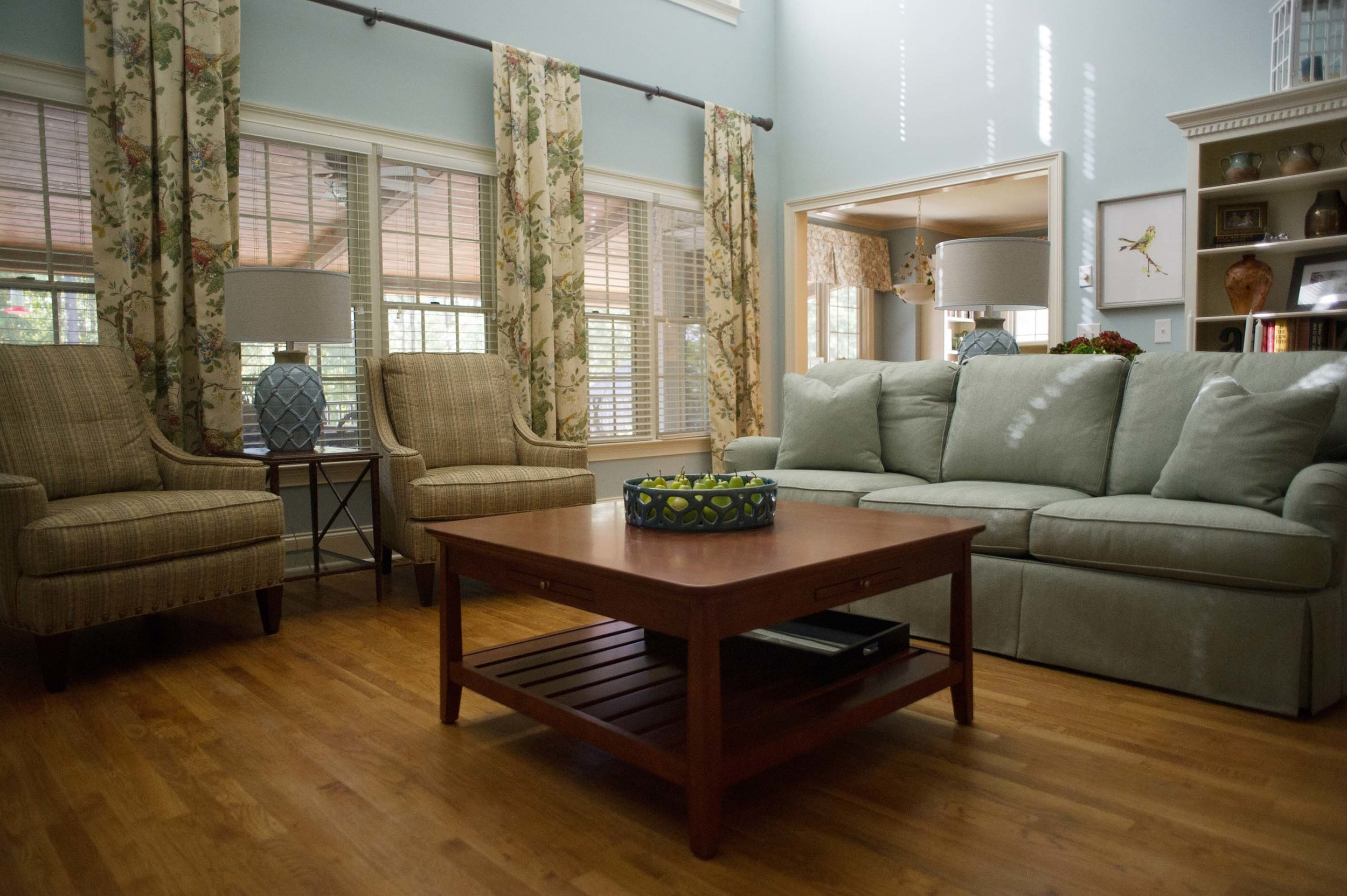 Living room with hardwood floor, wooden center table, sofa and armchair