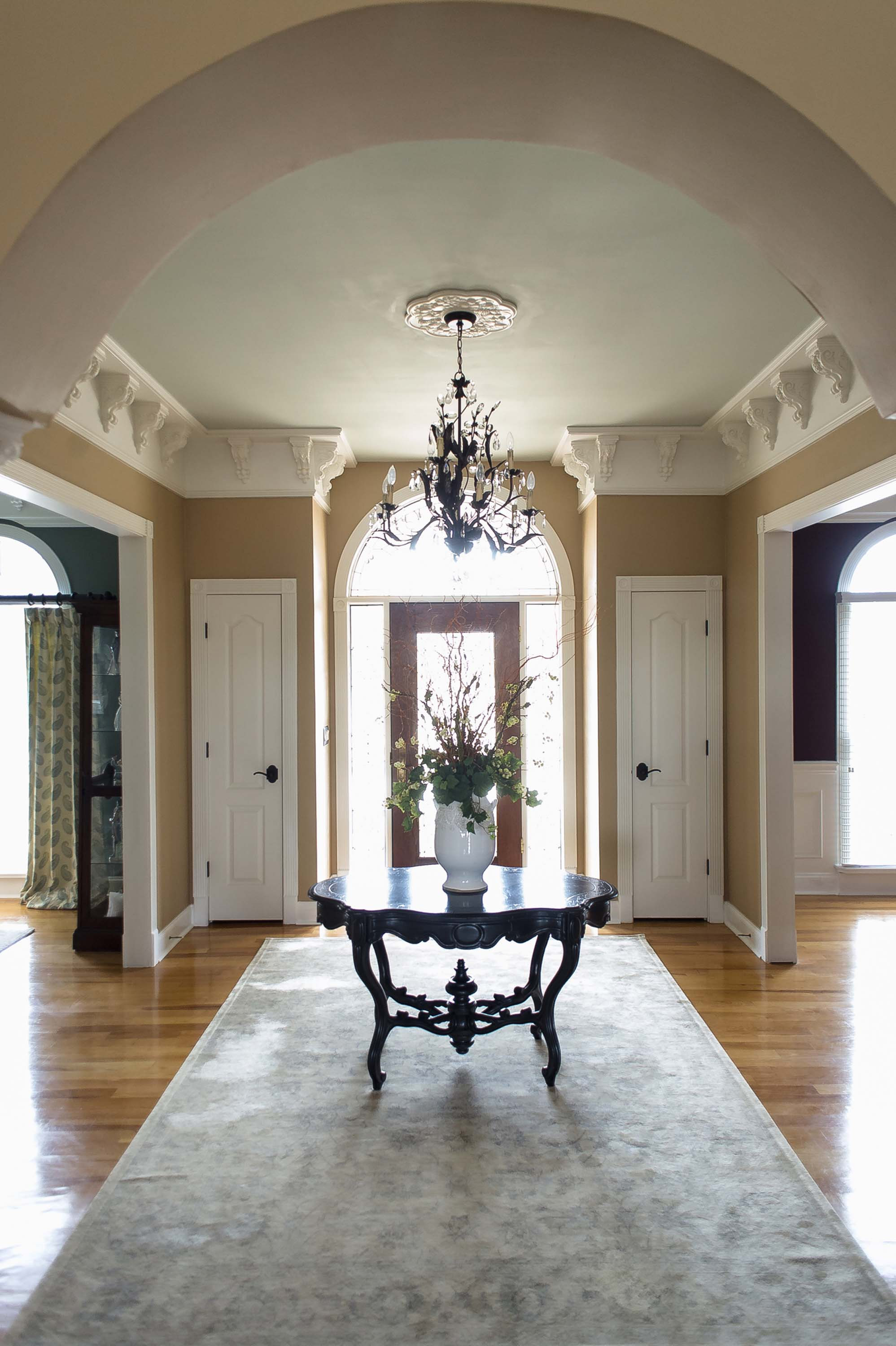 House interior entrance with wooden round table, chandelier and hardwood floor