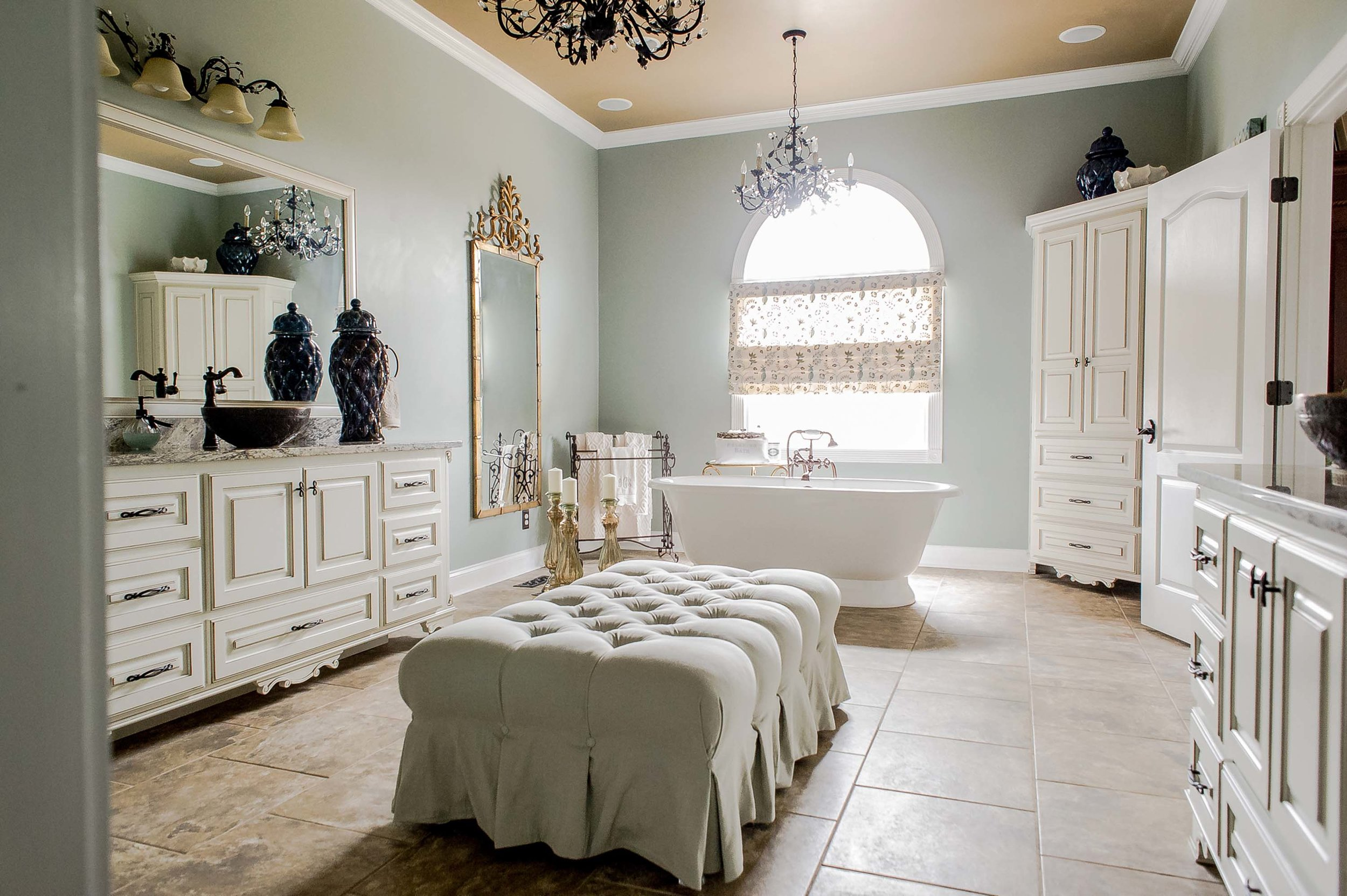 Bathroom with bathtub, white drawers, cabinet, mirror and chandelier