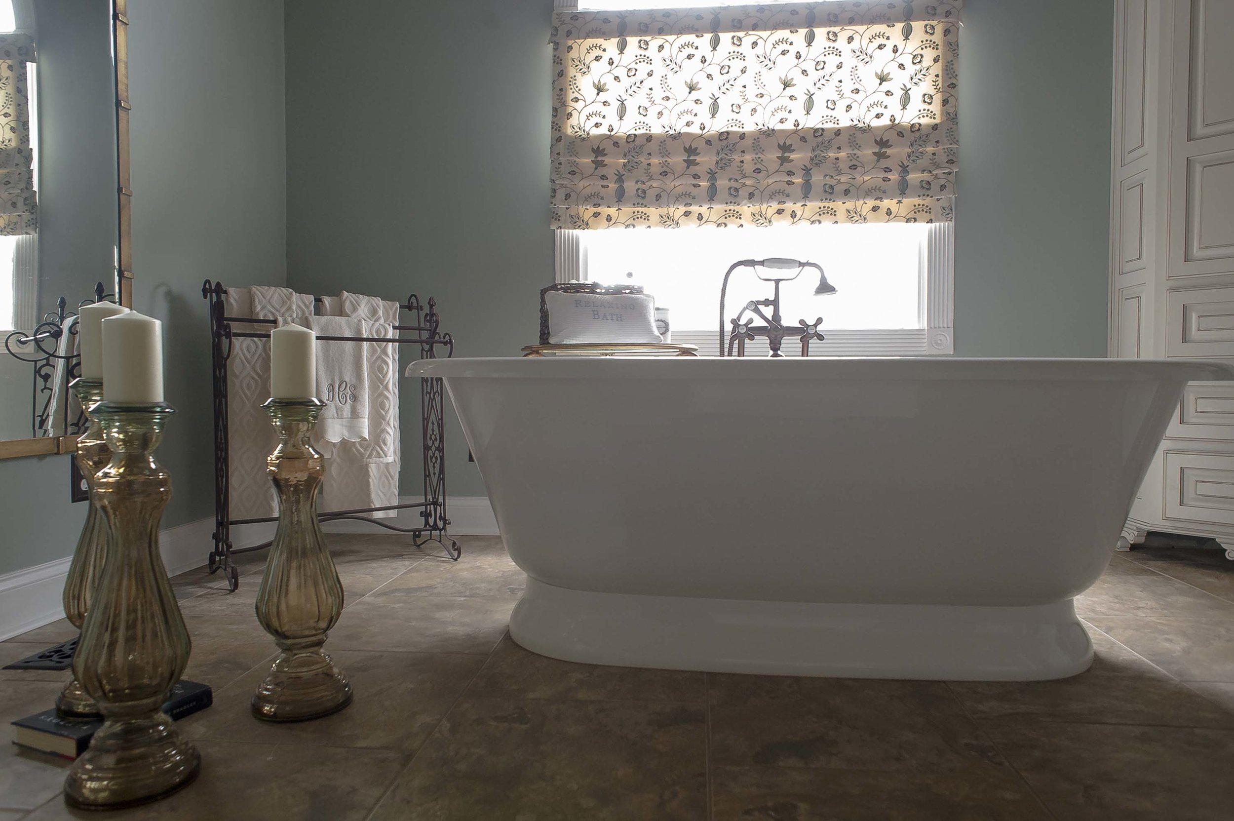 Bathroom with white bathtub, wax candles on the candle holder