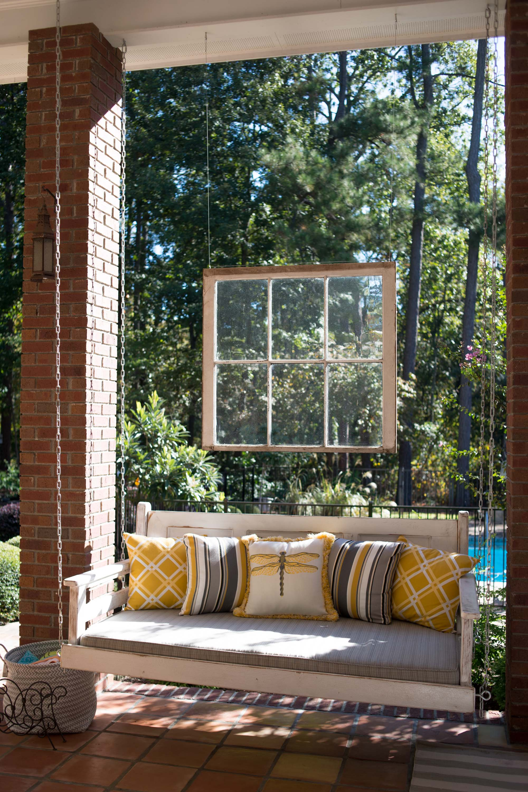 Outdoor patio with hanging  sofa and brown floor tiles