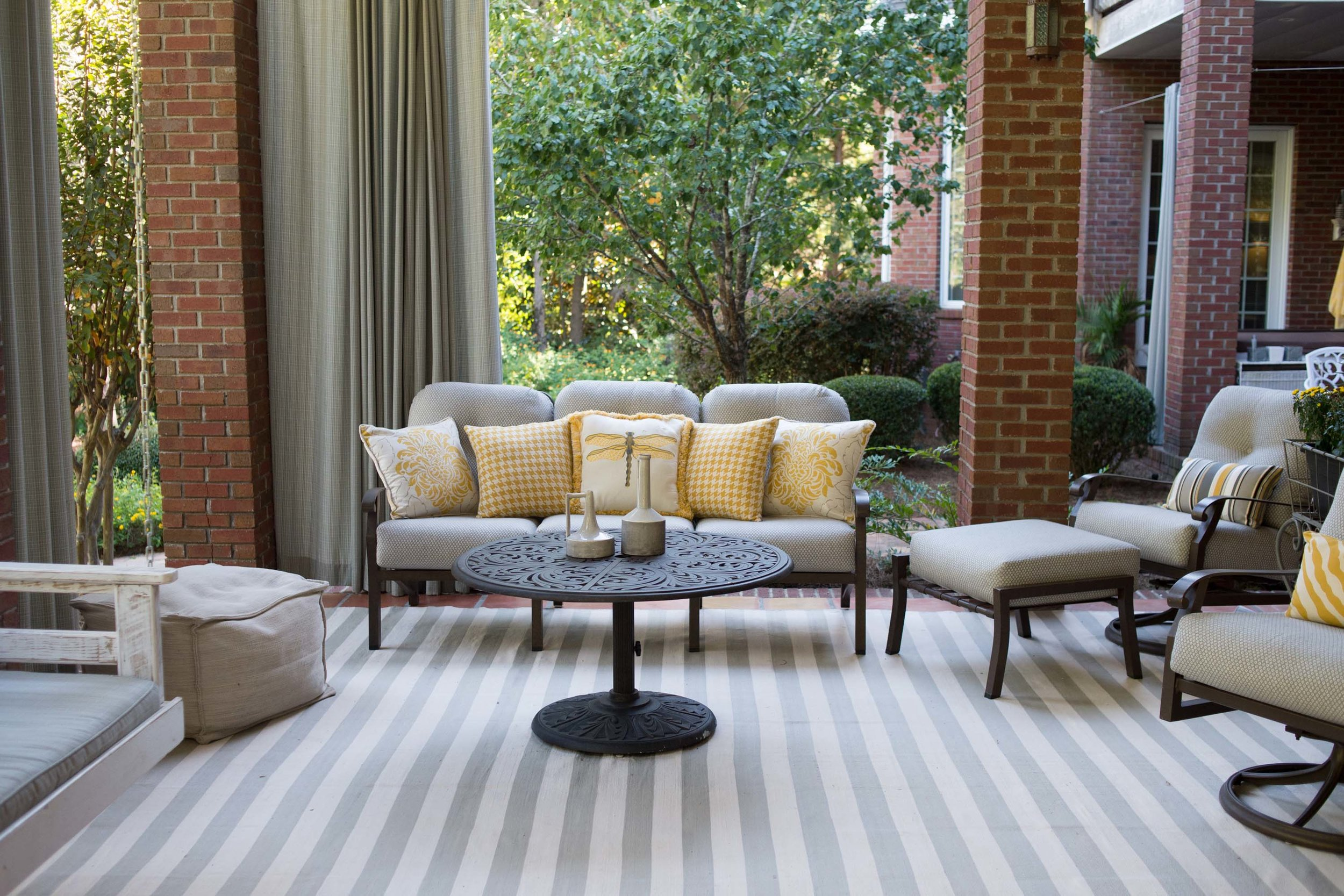 Outdoor patio with sofa, armchair and large striped carpet