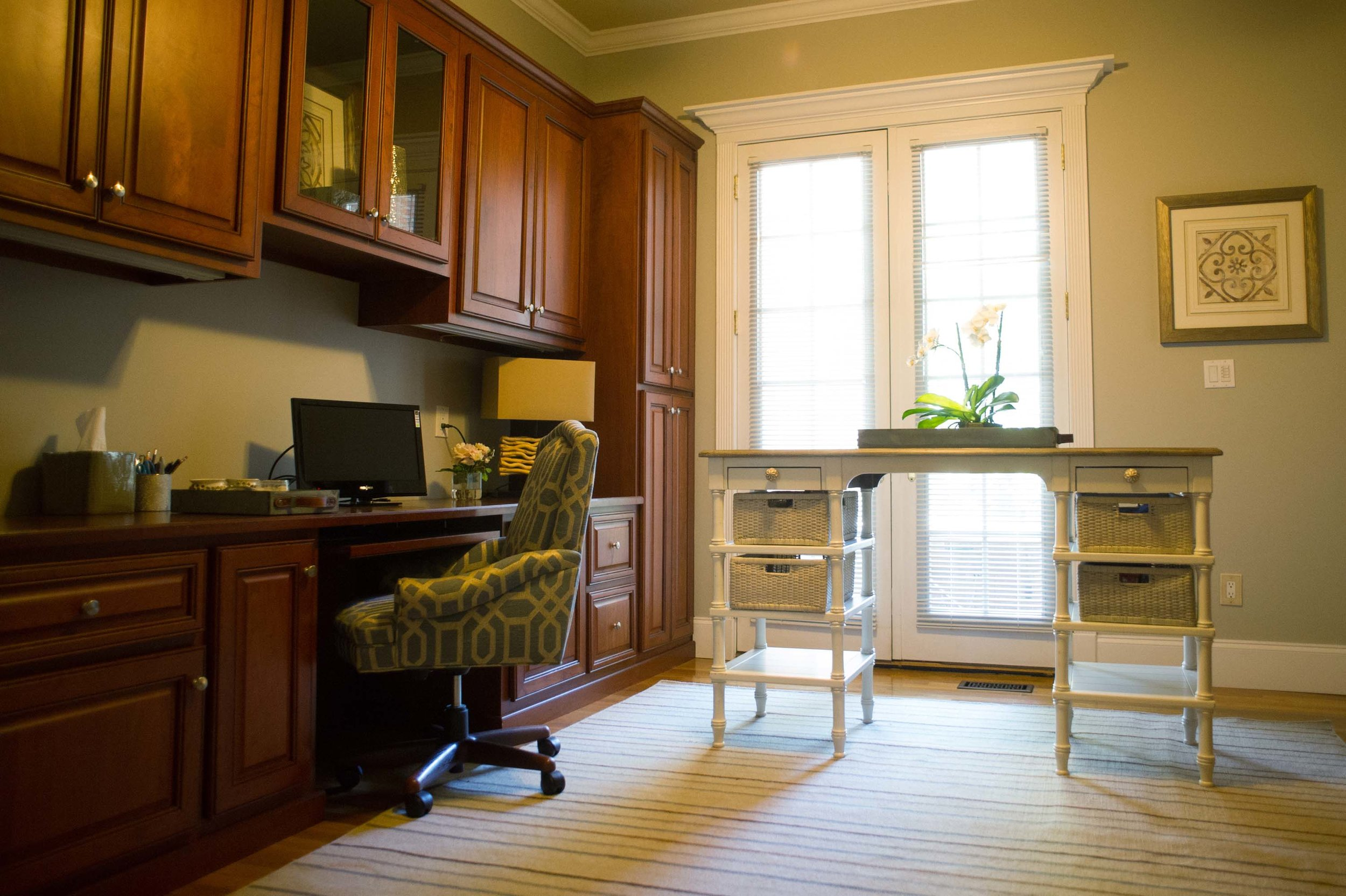 House interior with wooden cabinet, table, office chair and a desktop