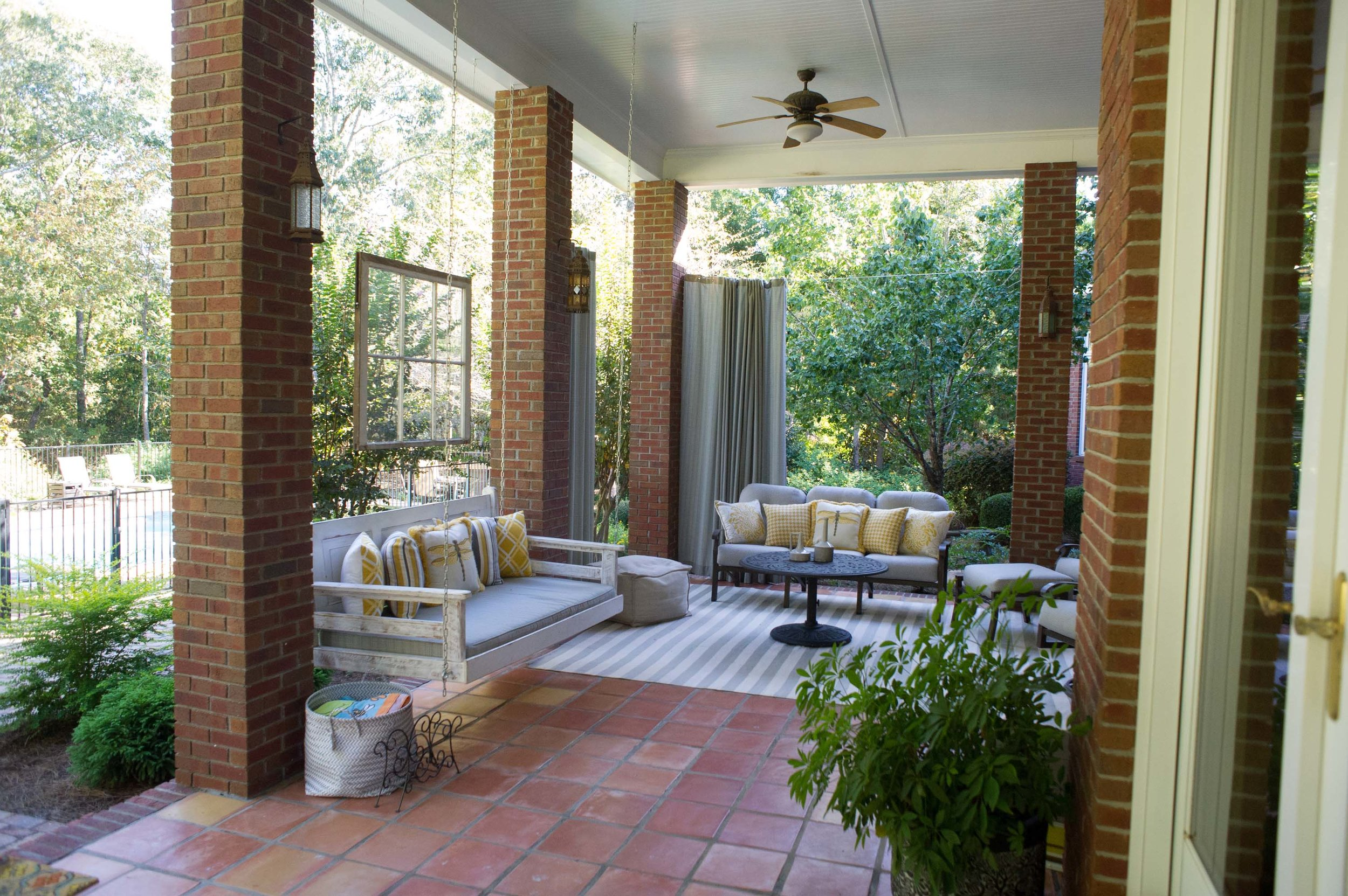 Outdoor patio with green plant, sofa set, customized hanging sofa and ceiling fan