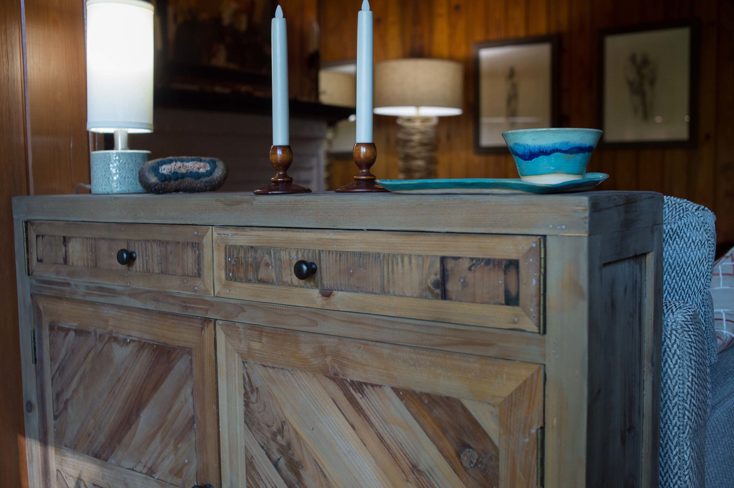 Wooden Buffet behind Sofa with small lamp, candlesticks and accessories.