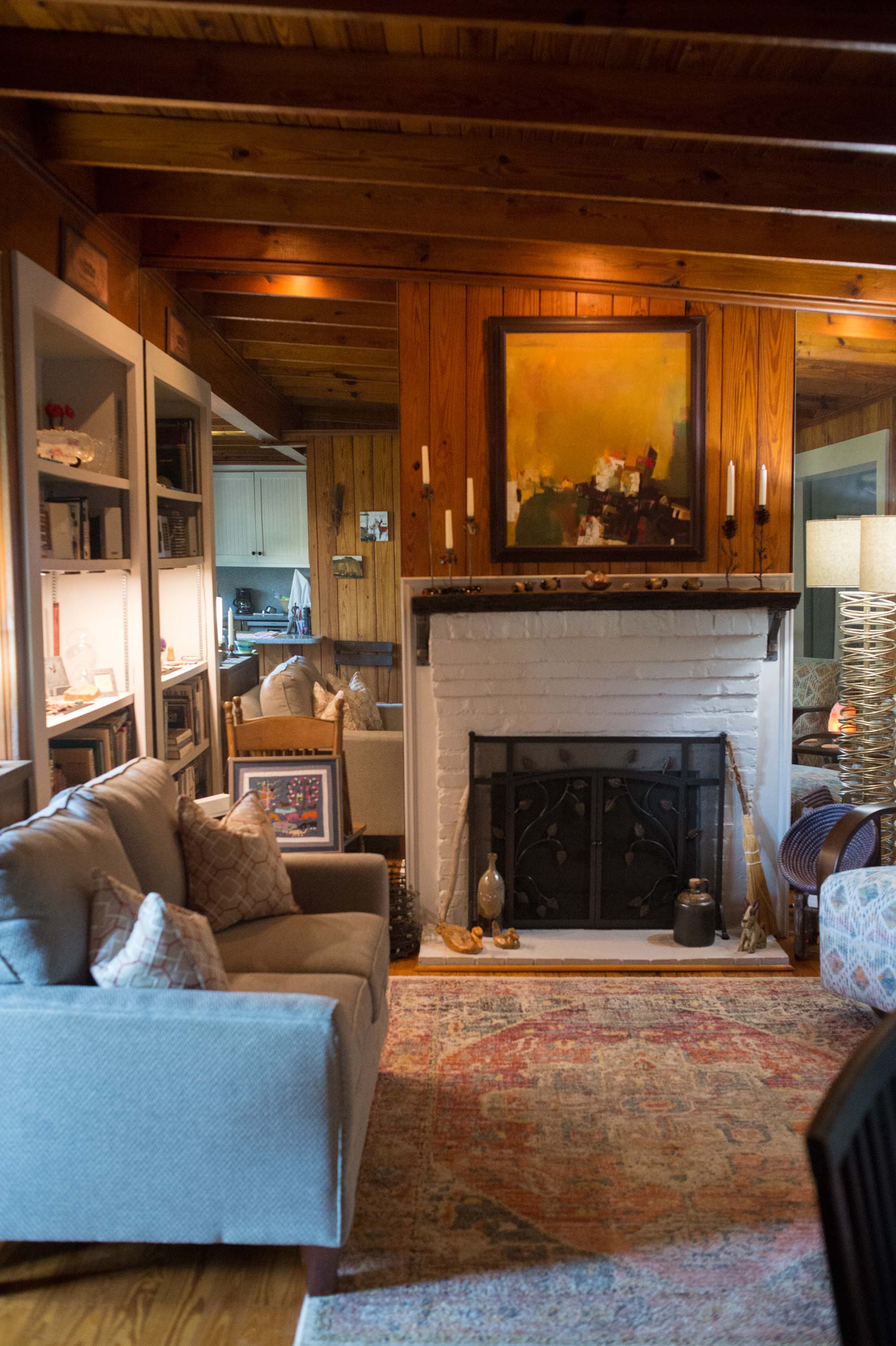 Living Room Fireplace with Sofa, Candlesticks, Artwork and Large Loloi Area Rug