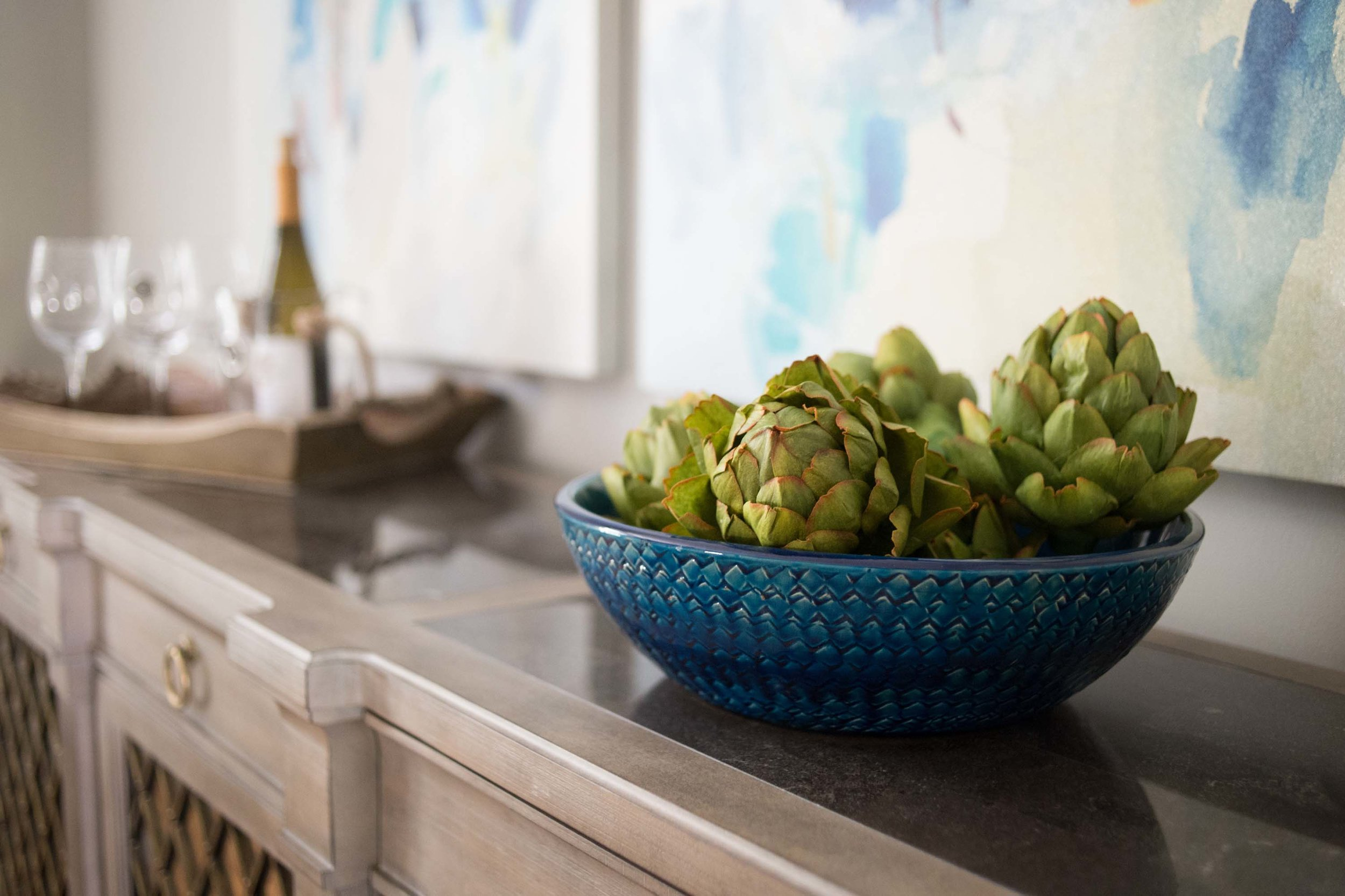 Accessories for Buffet that include artichokes, blue bowl & wine glasses