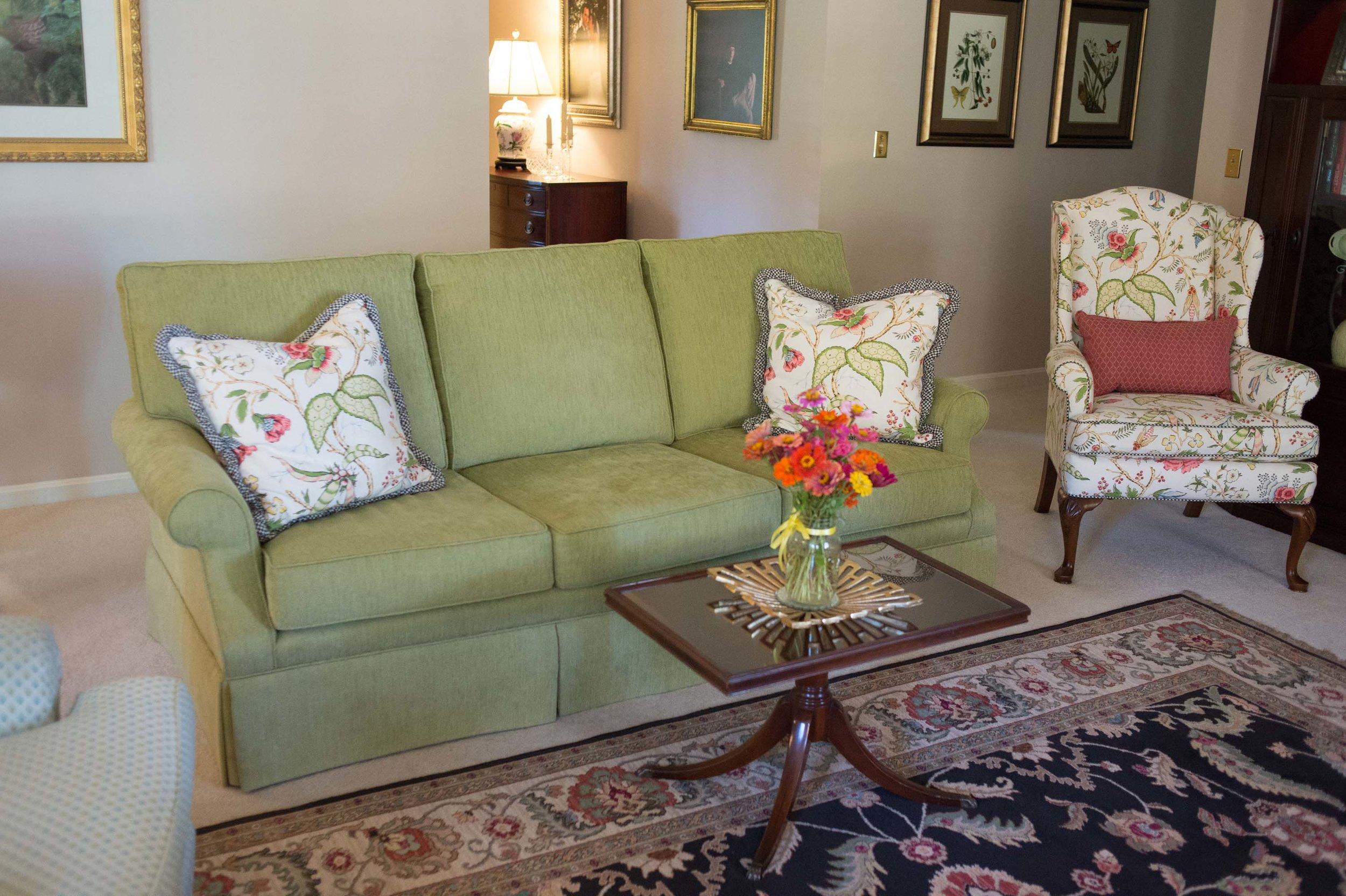 Living Room Sofa, Printed Pillows, Large Area Rug, Fresh Flowers & Coffee Table
