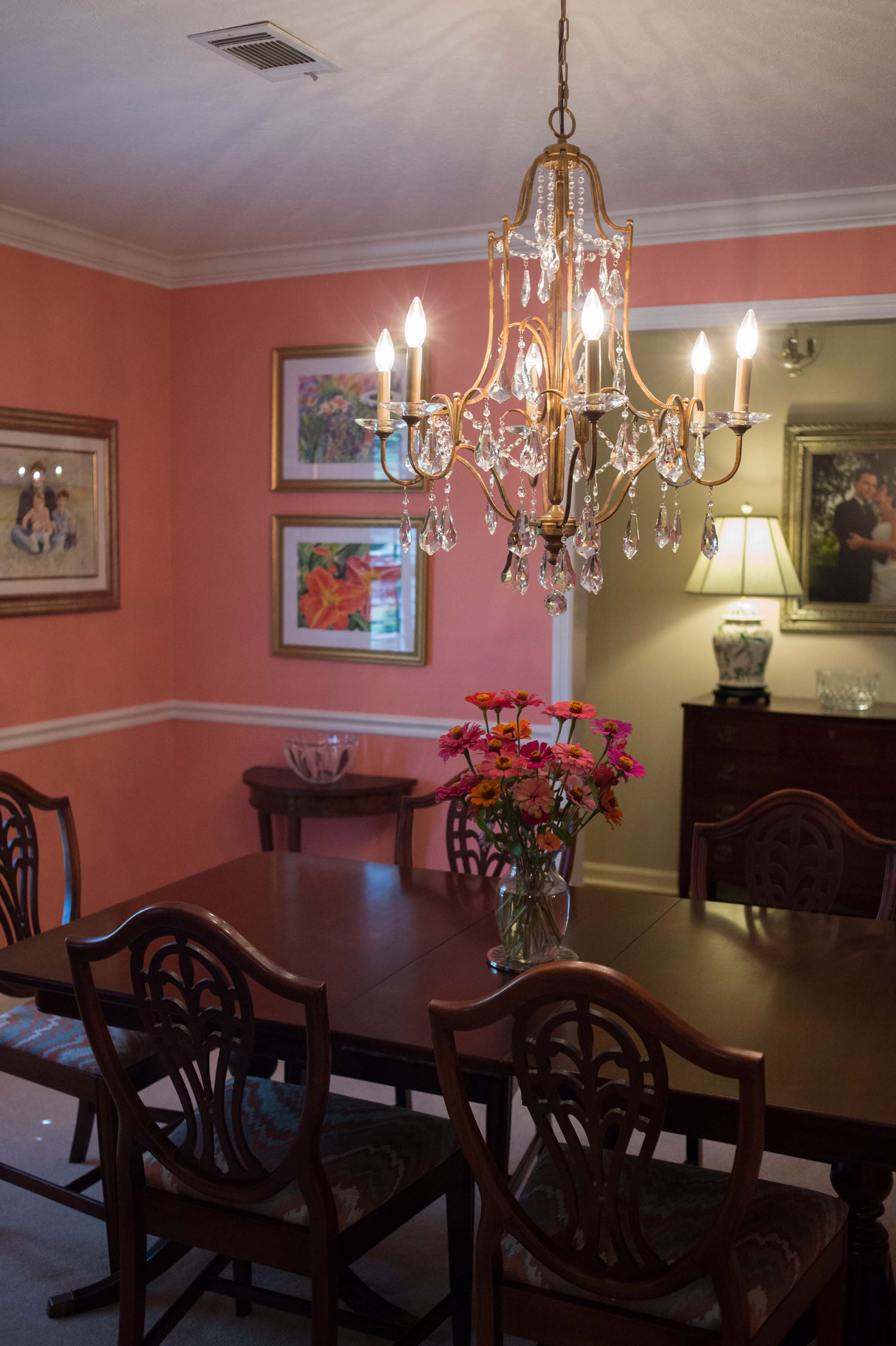 Pink Dining Room with Chandelier, Artwork and Fresh Flowers