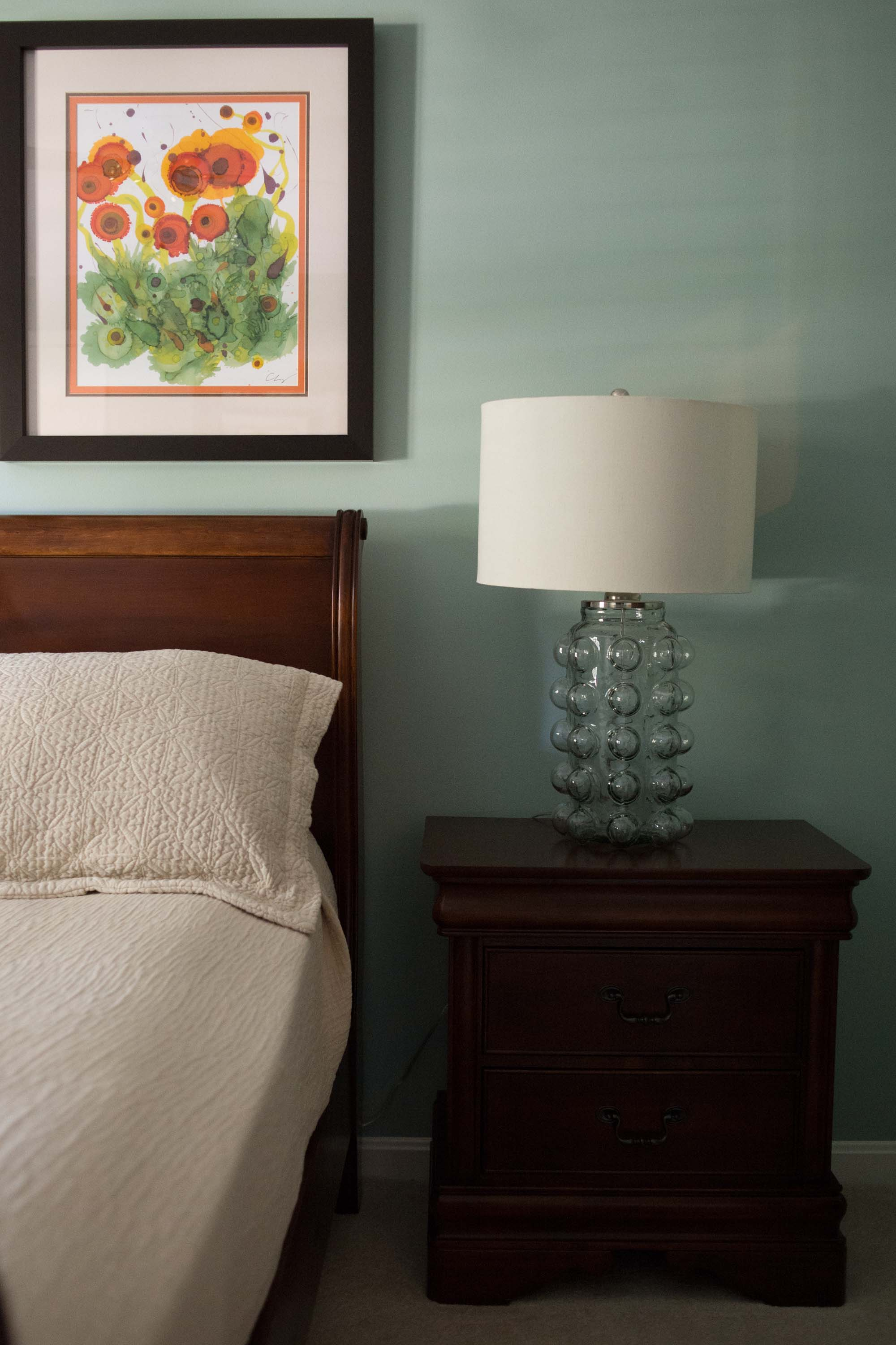 Blue Guest Bedroom with Floral Artwork and Lamp