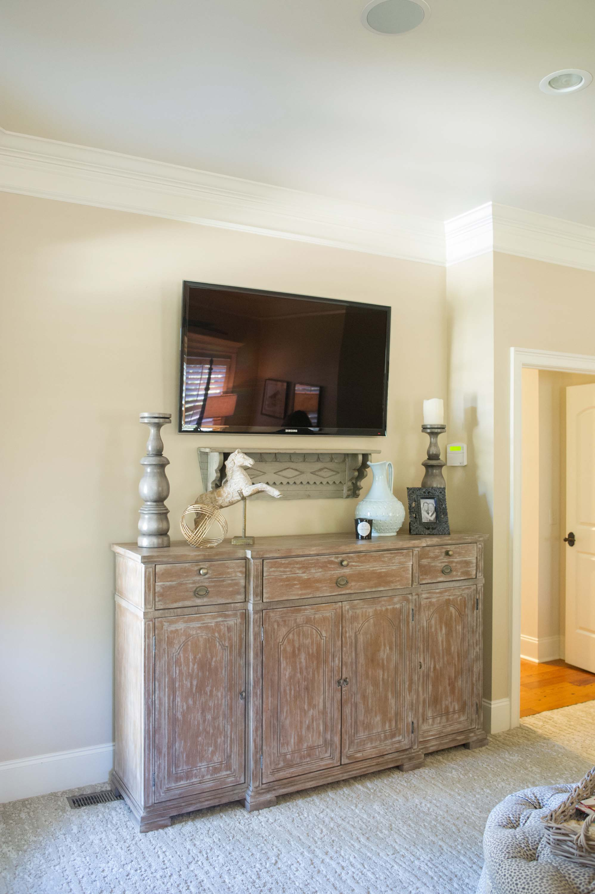 Wooden Chest with TV Hanging Above and Accessories