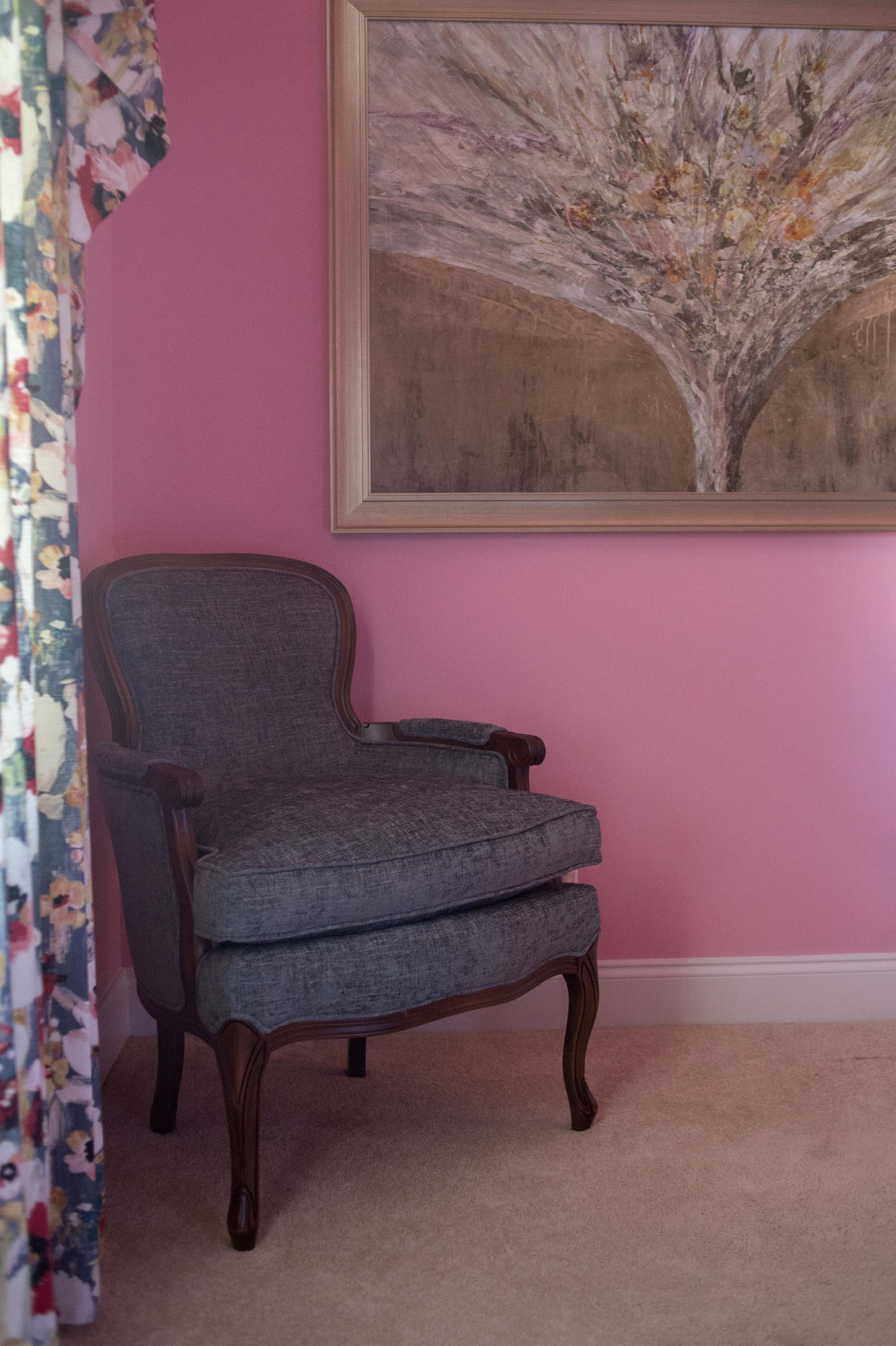 Upholstered Chair on Pink Walls in Guest Bedroom