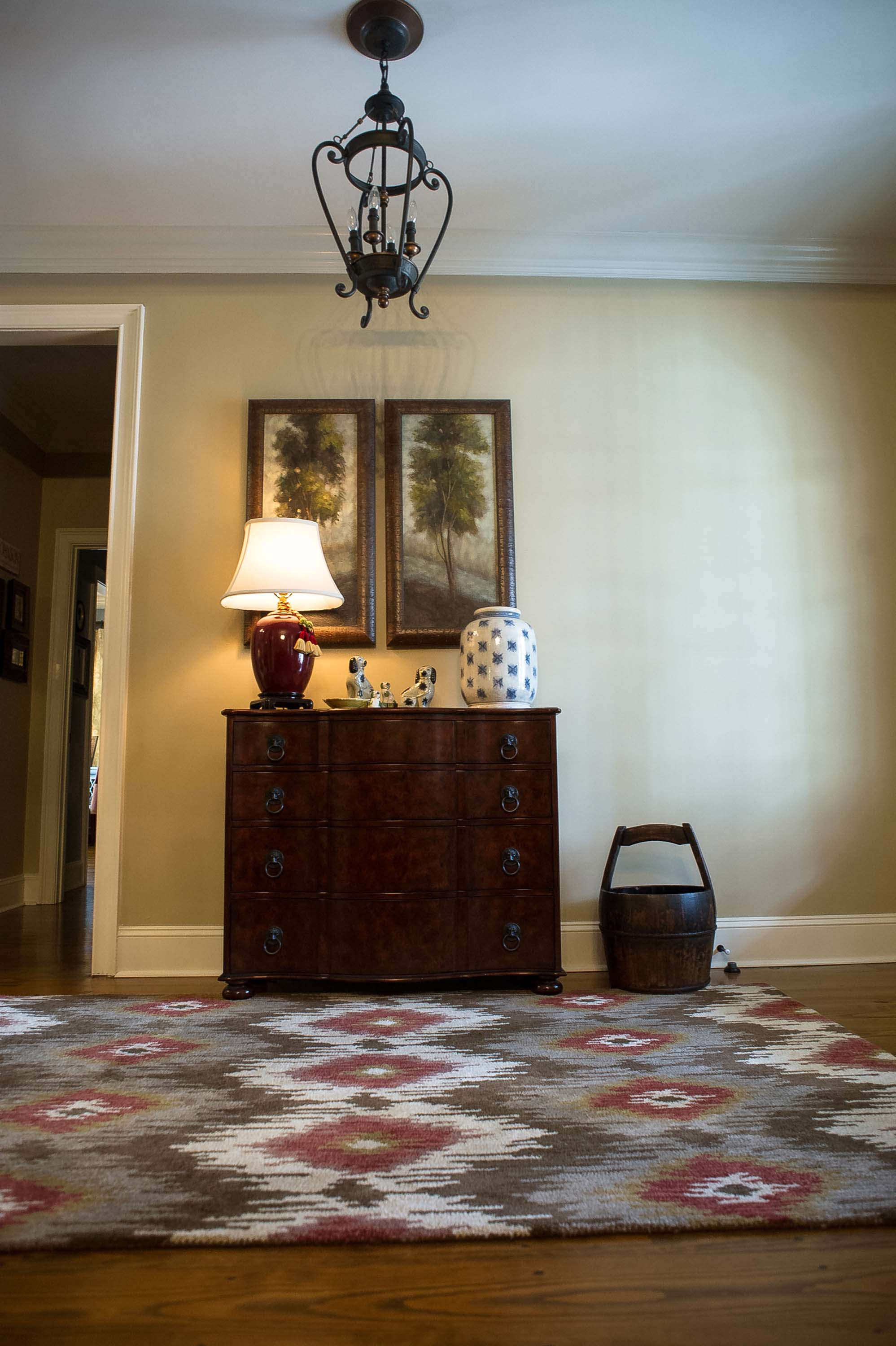 Foyer Rug with Casegood Piece, Artwork and Chandelier