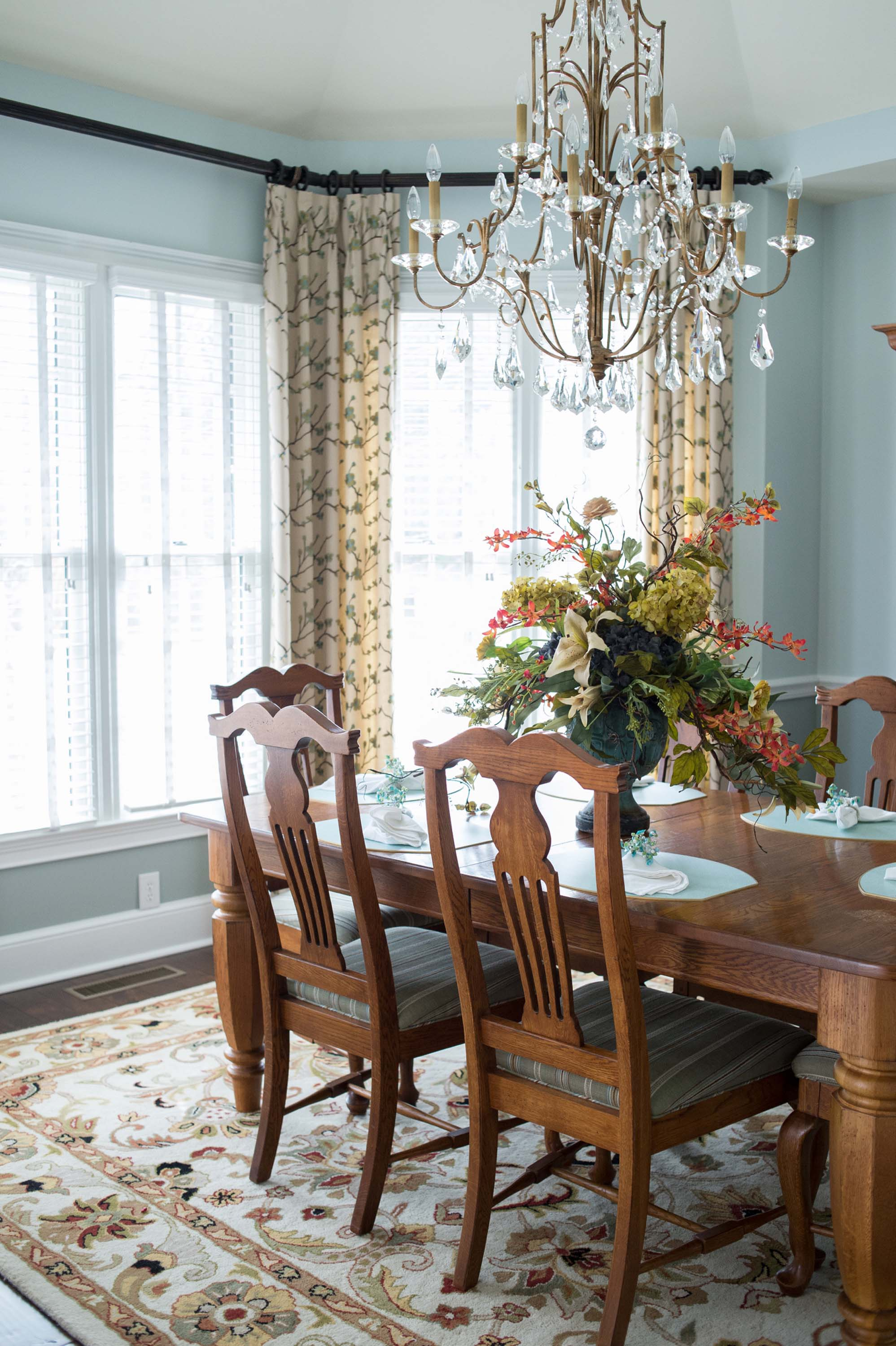 Custom Dining Room Window Treatments with Chandelier, Large Area Rug and Floral Centerpiece