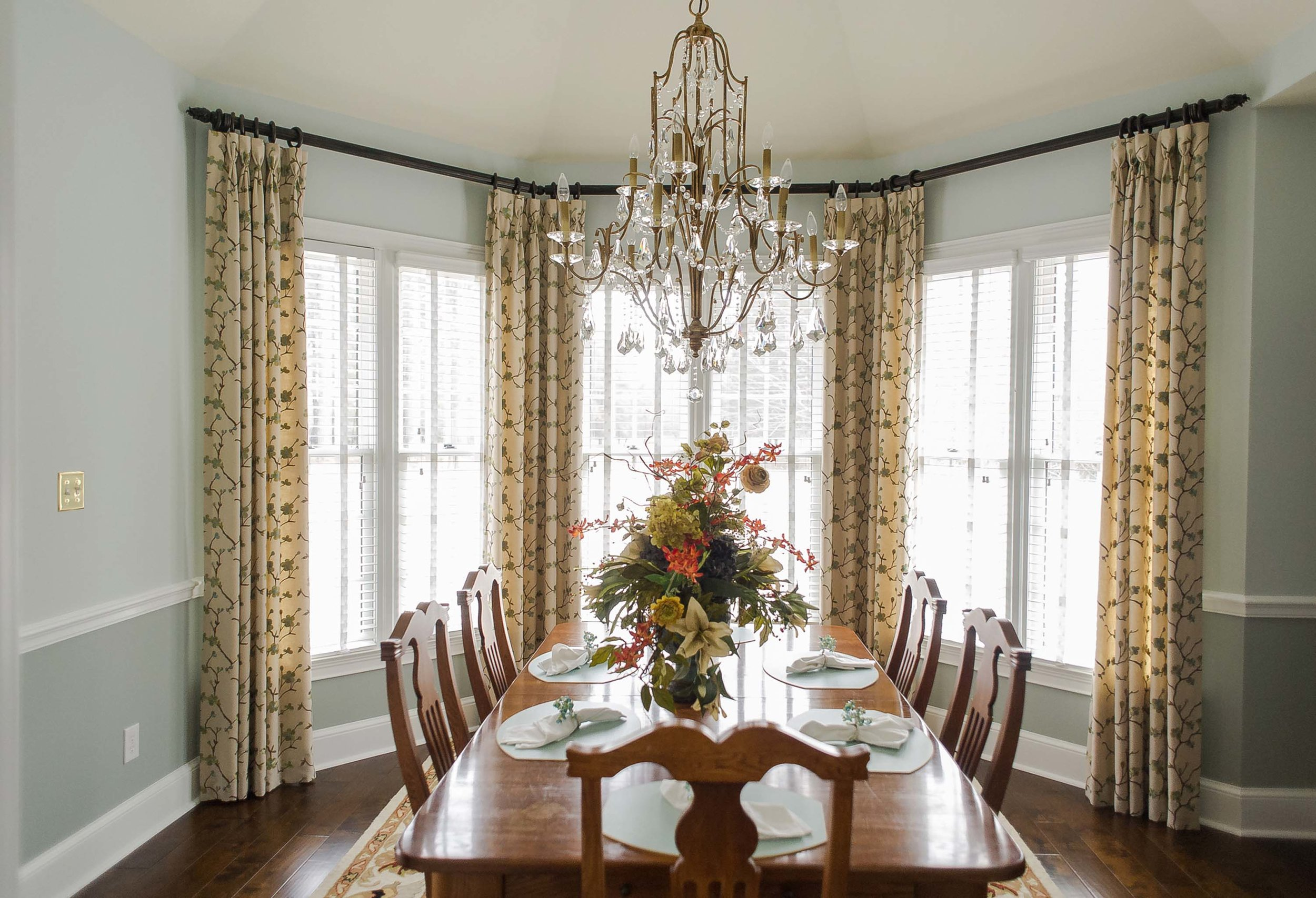 Large Open window with shutters, custom window treatments and floral table arrangement