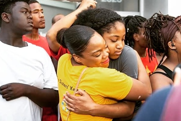 Kina hugging a young woman during a youth rally.