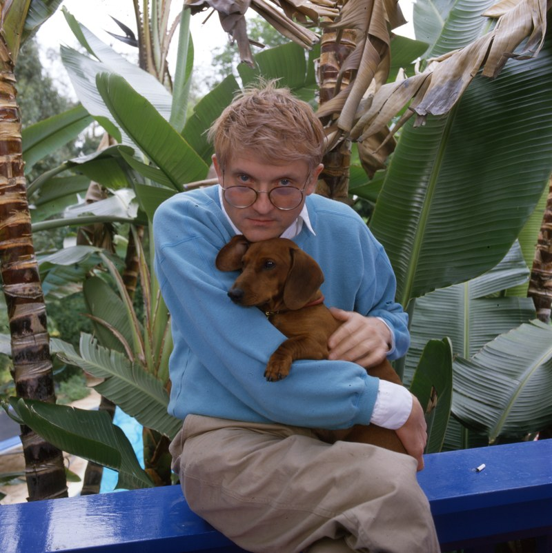Arguably the most famous living artist today, U.K.-born David Hockney is seen holding one of his beloved short-legged dachshunds.