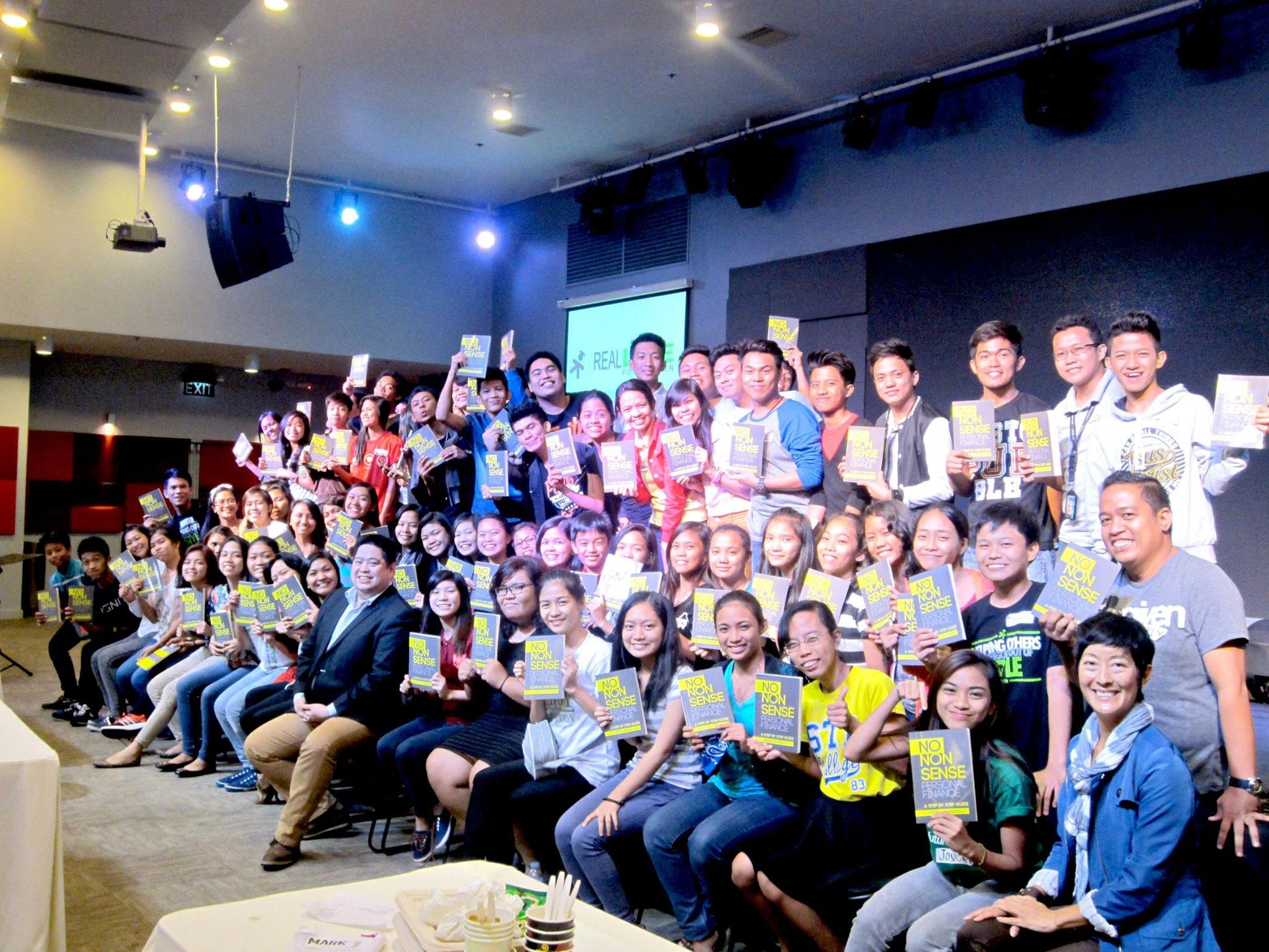 """Randell Tiongson with Real LIFE scholars when he did a financial training for them in 2015. He also gave them copies of his book """"No Non-Sense Personal Finance""""."""