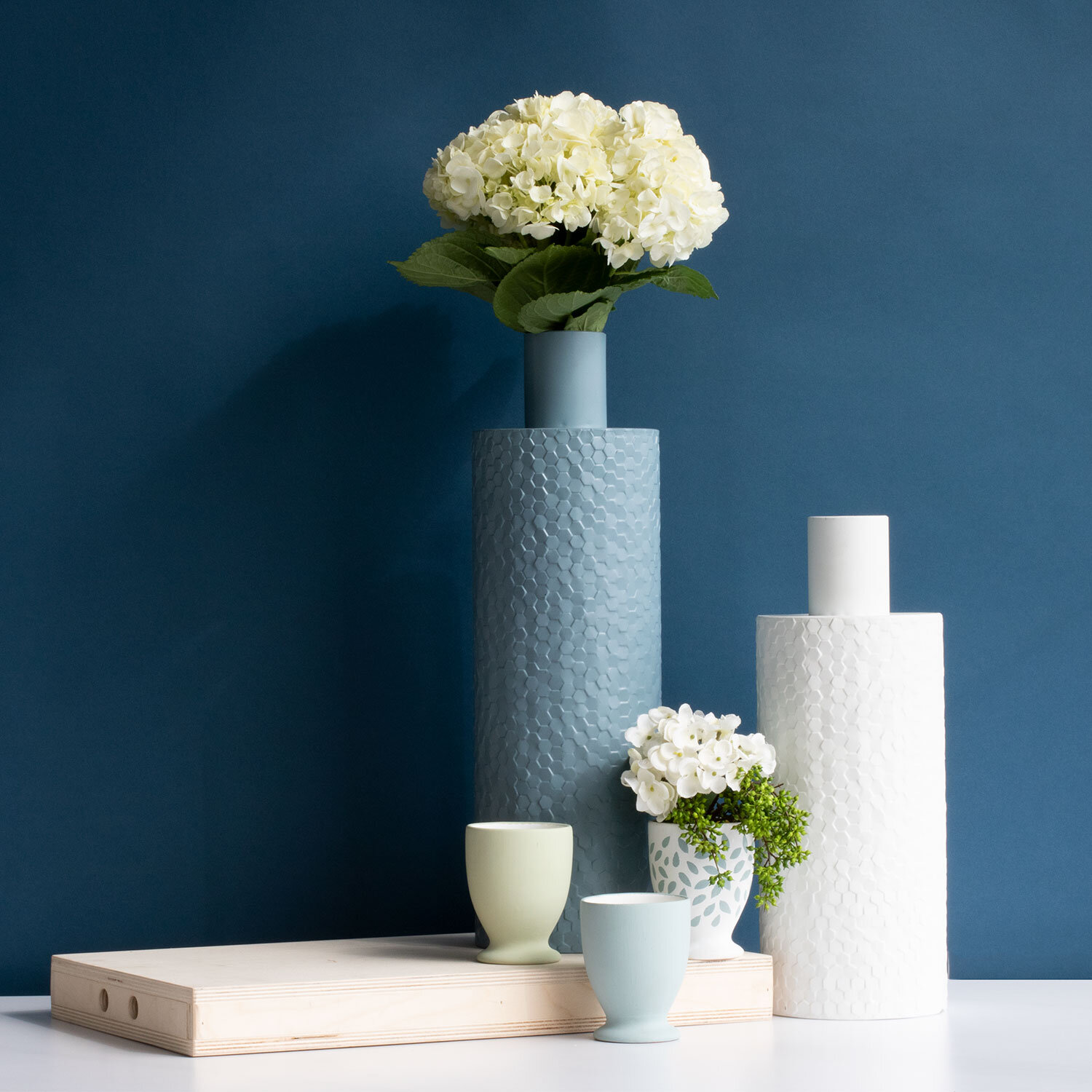 Items Shown:  Lanky Vase Blue ,  Lanky Vase White ,  Footed Planter, 3 colors