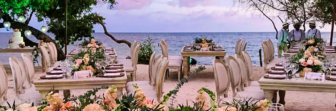 view of tables with flowers by the beach for a wedding ready to start in cartagena, colombia, casamar cartagena