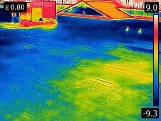 Infrared view of water trapped under a flat roof. The yellow and red areas are actually the water since it was the warmer area. Infrared cameras give us the ability to find hidden or trapped water.