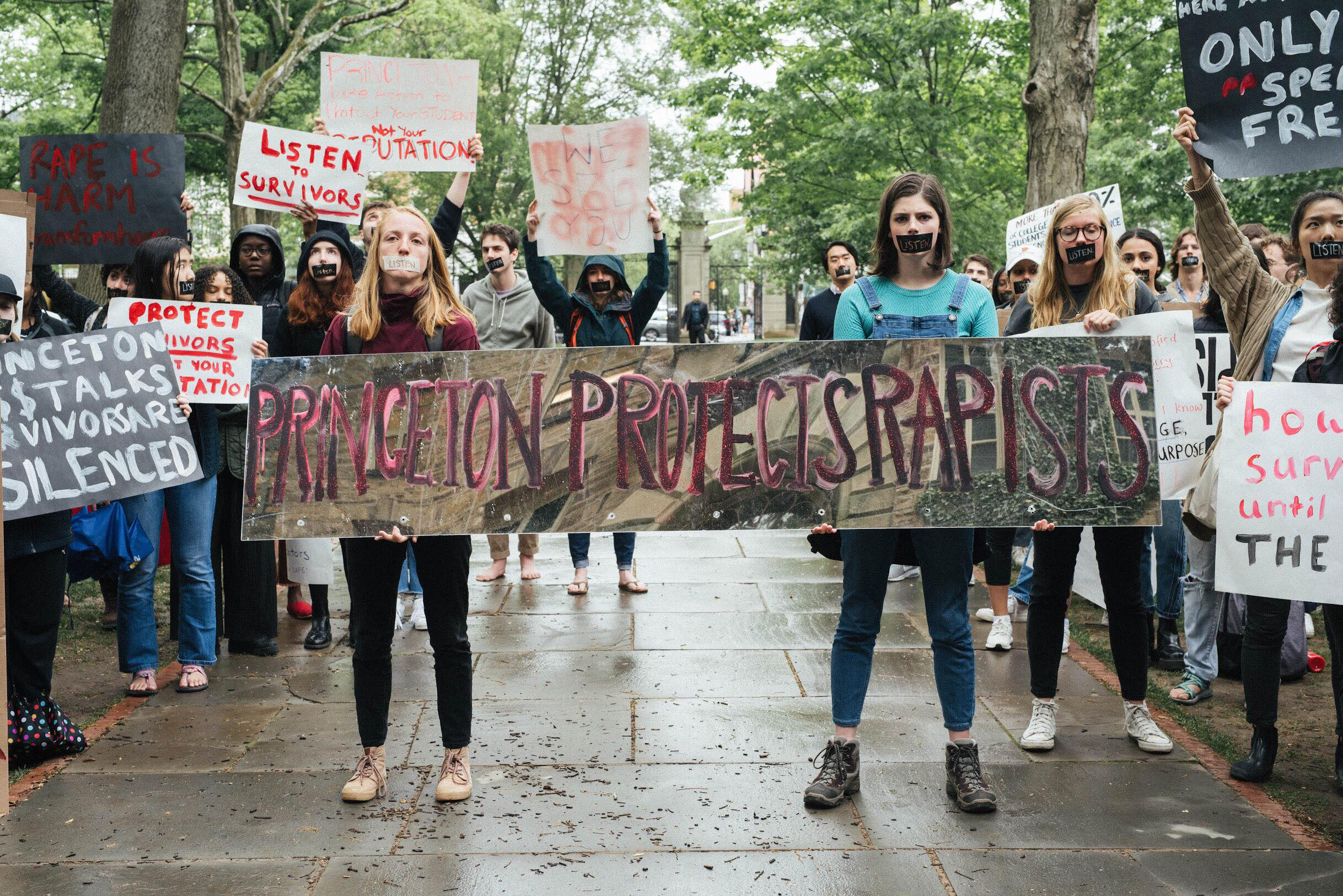 "Image of two people holding a mirror that reads ""Princeton Protects Rapists"" facing Nassau Hall with ""Listen"" tape on their mouth. They are surrounded by students holding other signs also with ""Listen"" tape."