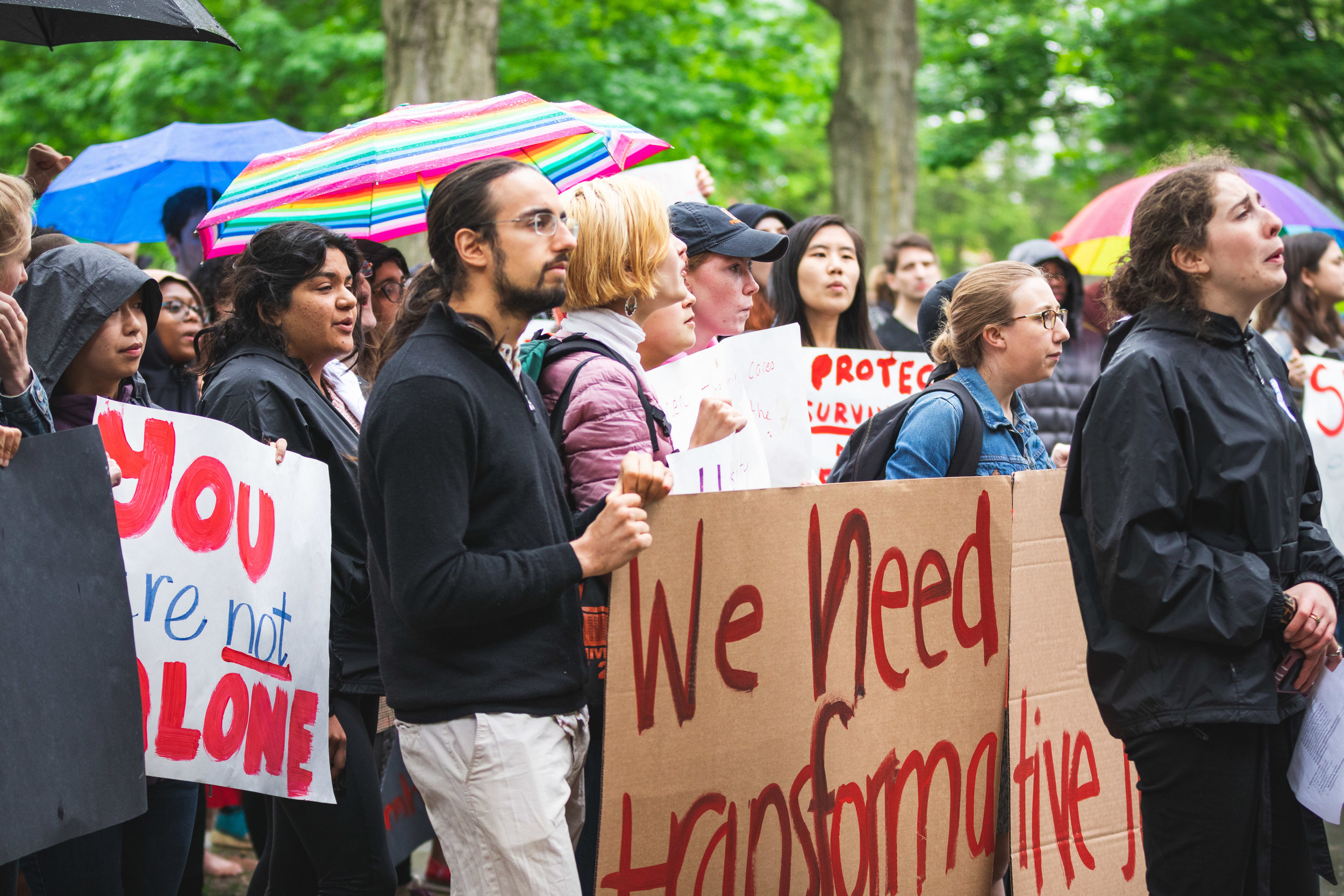 "Image of demonstrators with signs (""You are not alone"", ""We need transformative justice"") facing Nassau Hall, holding umbrellas and chanting."