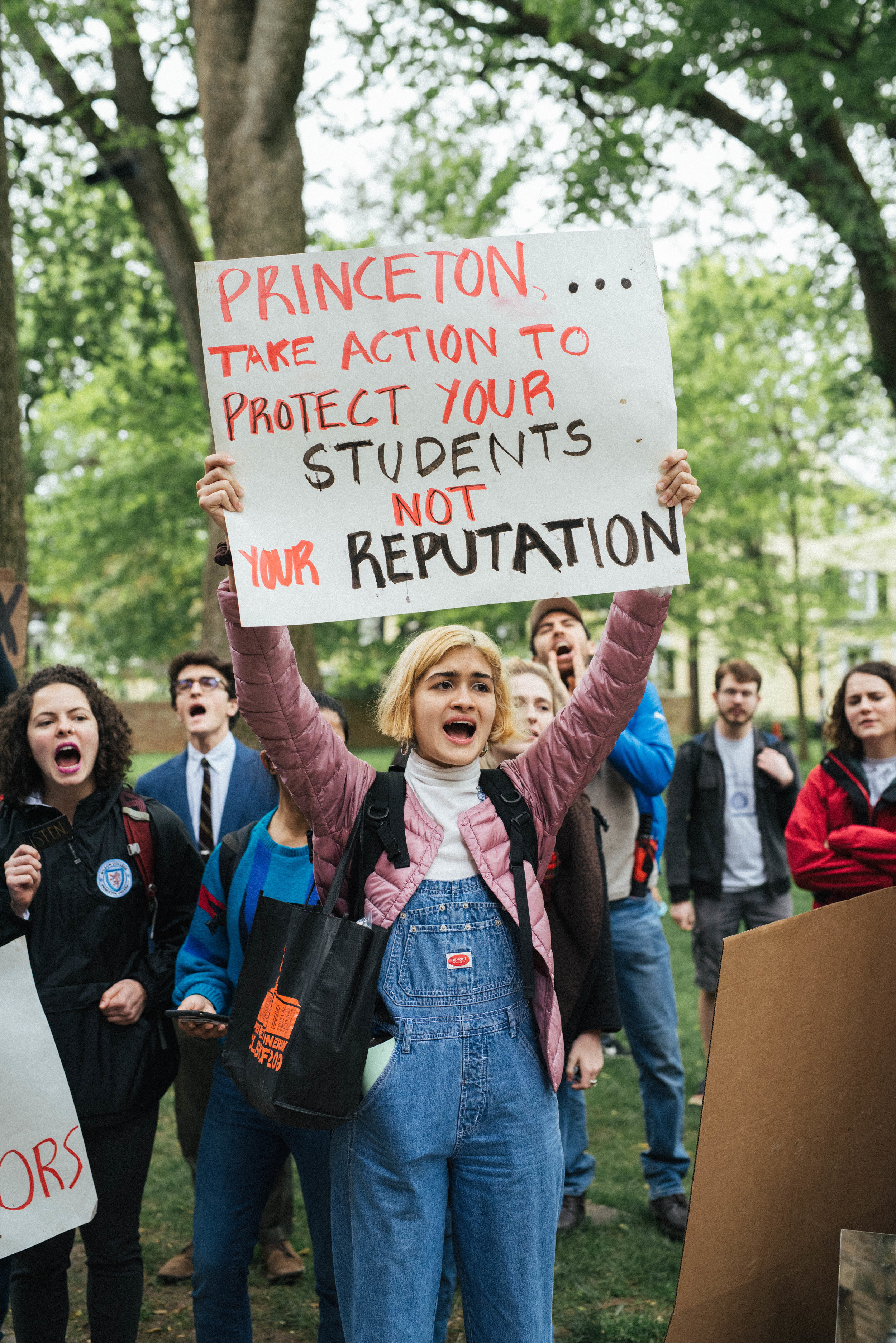 "Photo by Elizabeth Yu '19. Student holding a sign (""Princeton… take action to protect your students not your reputation"") and chanting."