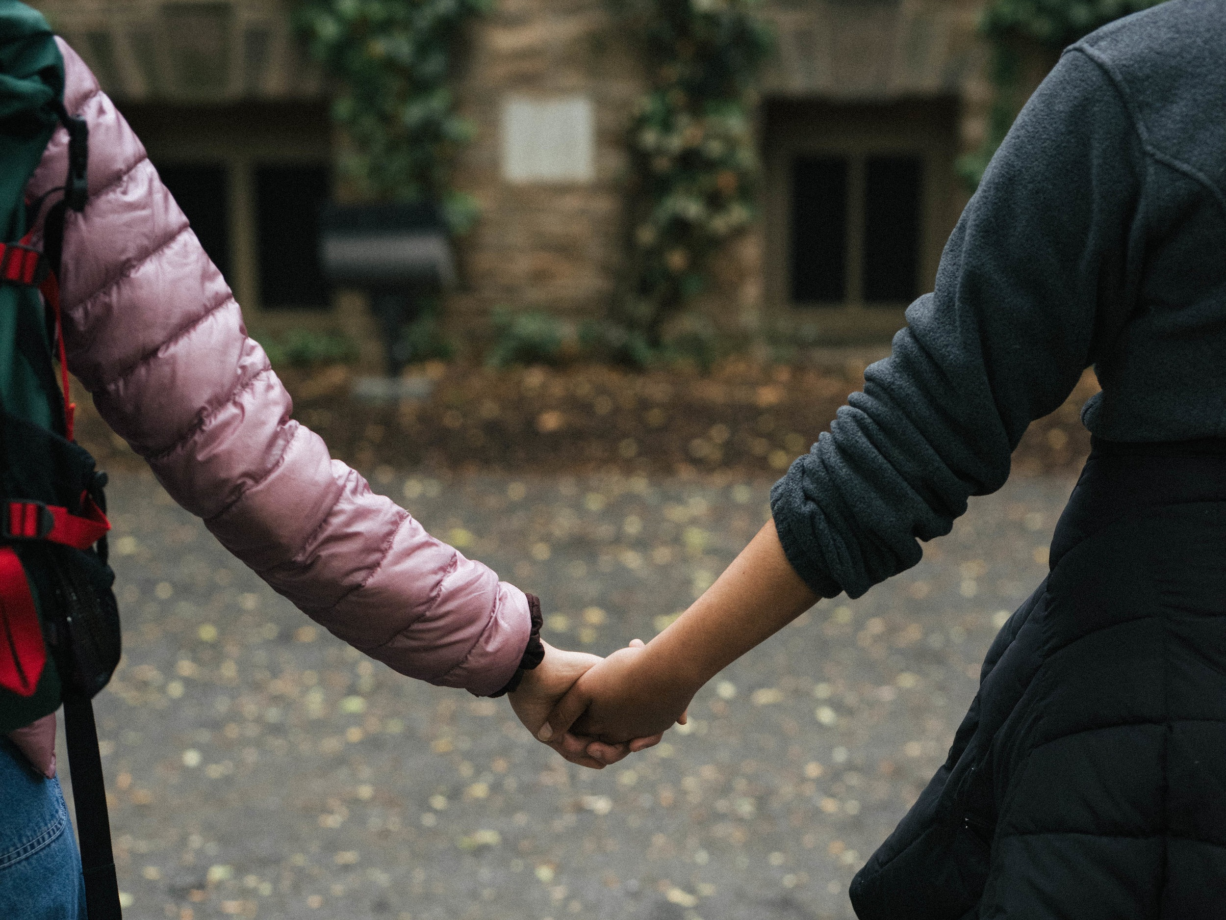 Two students linking hands in front of Nassau Hall during a demonstration in the light rain. Photo by Brad Spicher.
