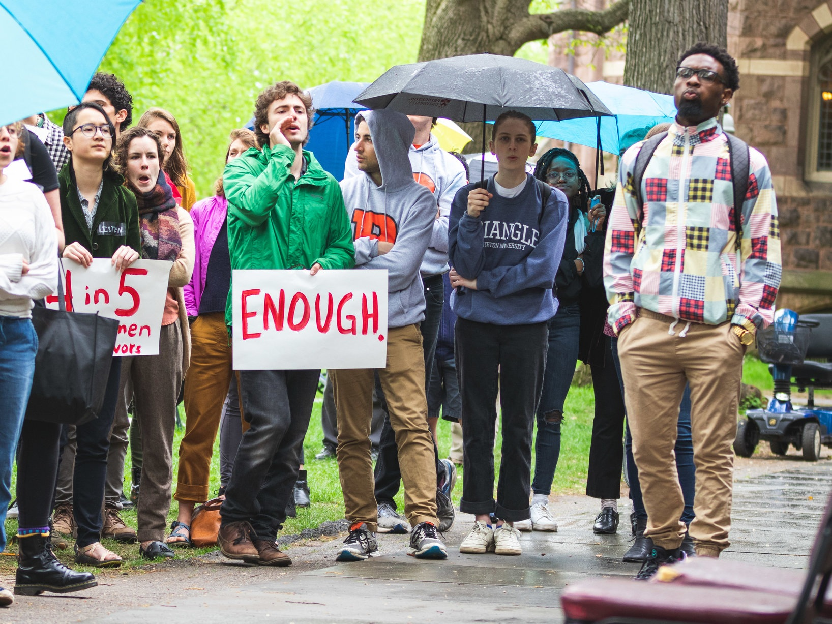 Students in light rain during the sit-in in front of Nassau Hall chanting. One person holds a sign that says 'ENOUGH.' in red lettering. Photo by Brad Spicher.