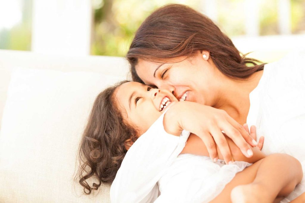 Happy mum hugging laughing young daughter