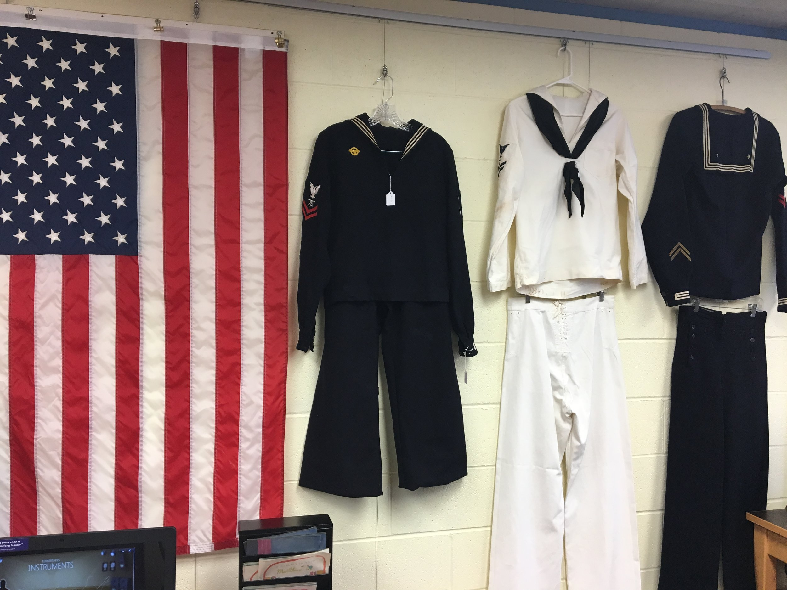 Naval uniforms are hung along the walls of the library. The uniforms were generously donated for display from local Manson and Chelan veterans.
