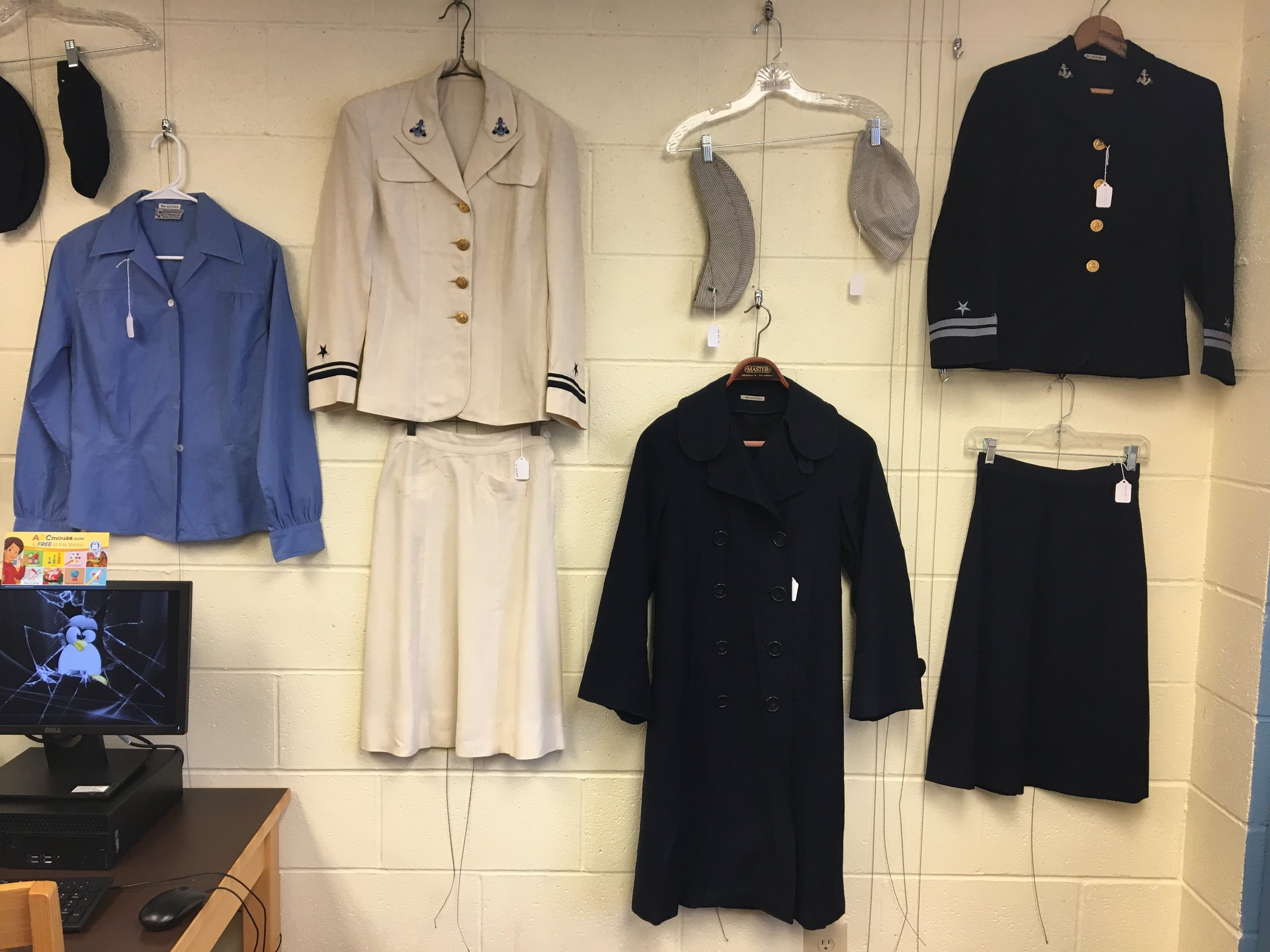 Additional uniforms on display with small tags detailing the time it was worn in service, the owner and which branch it is from.