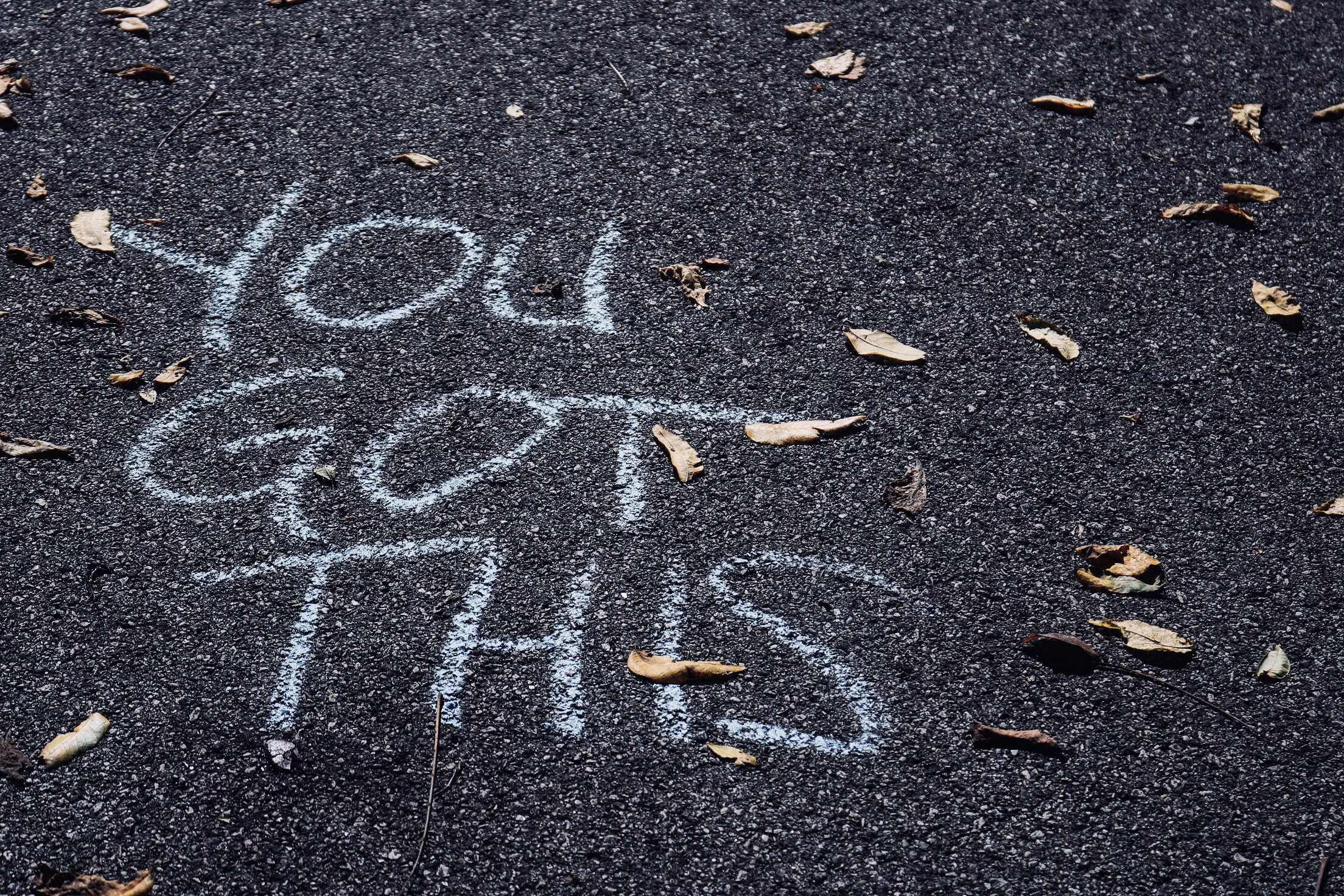 """Picture of a motivational message on asphalt that reads, """"you got this."""""""