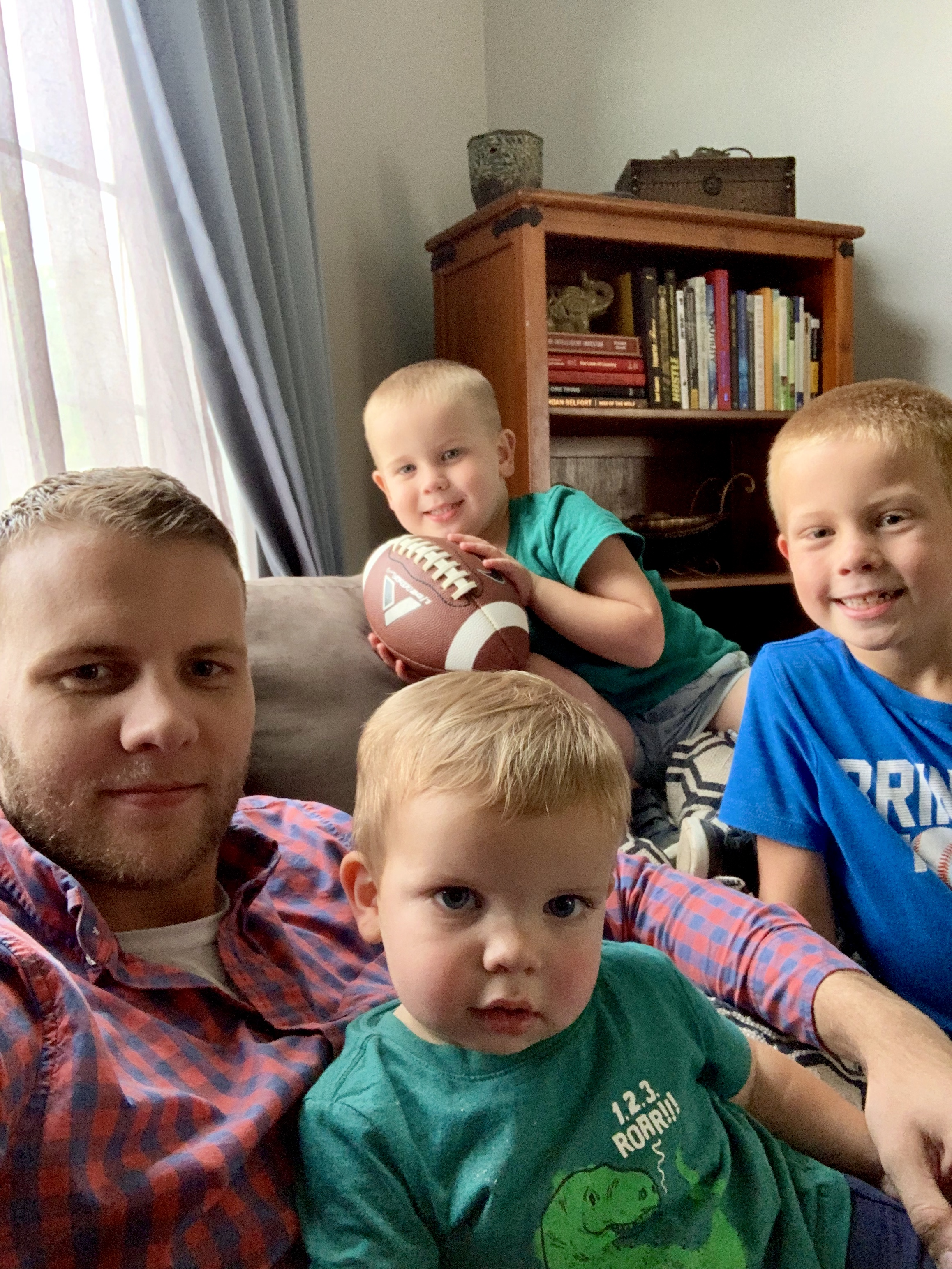 Image of nick sitting on the couch with his 3 boys after daycare.