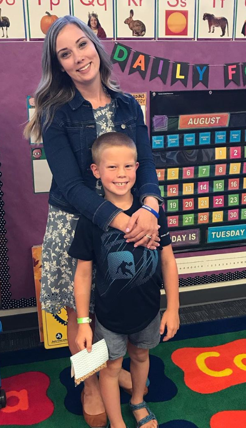 Image of Kayla and our son standing in her kindergarten classroom.