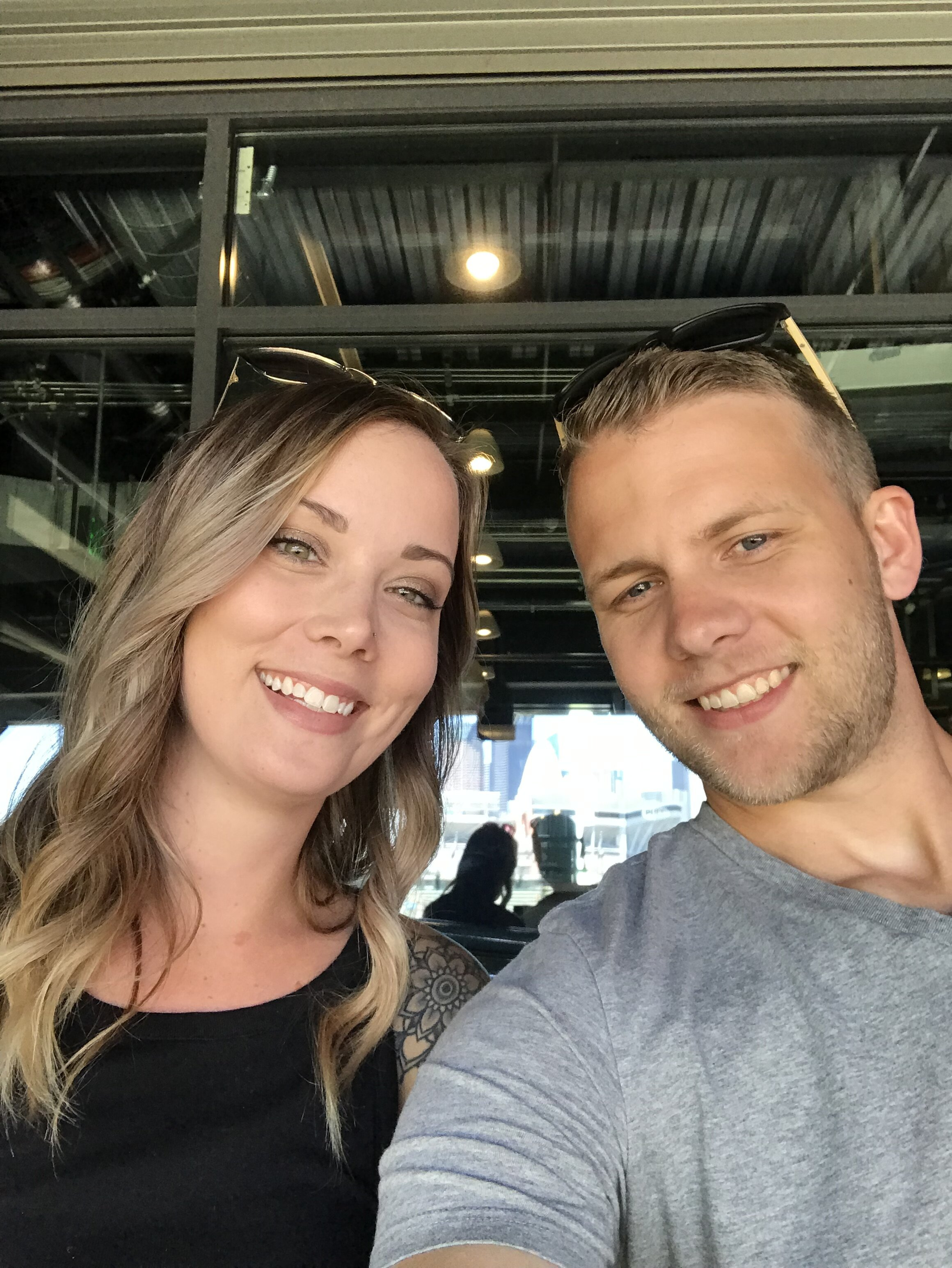 A picture of my wife and i at a baseball game.