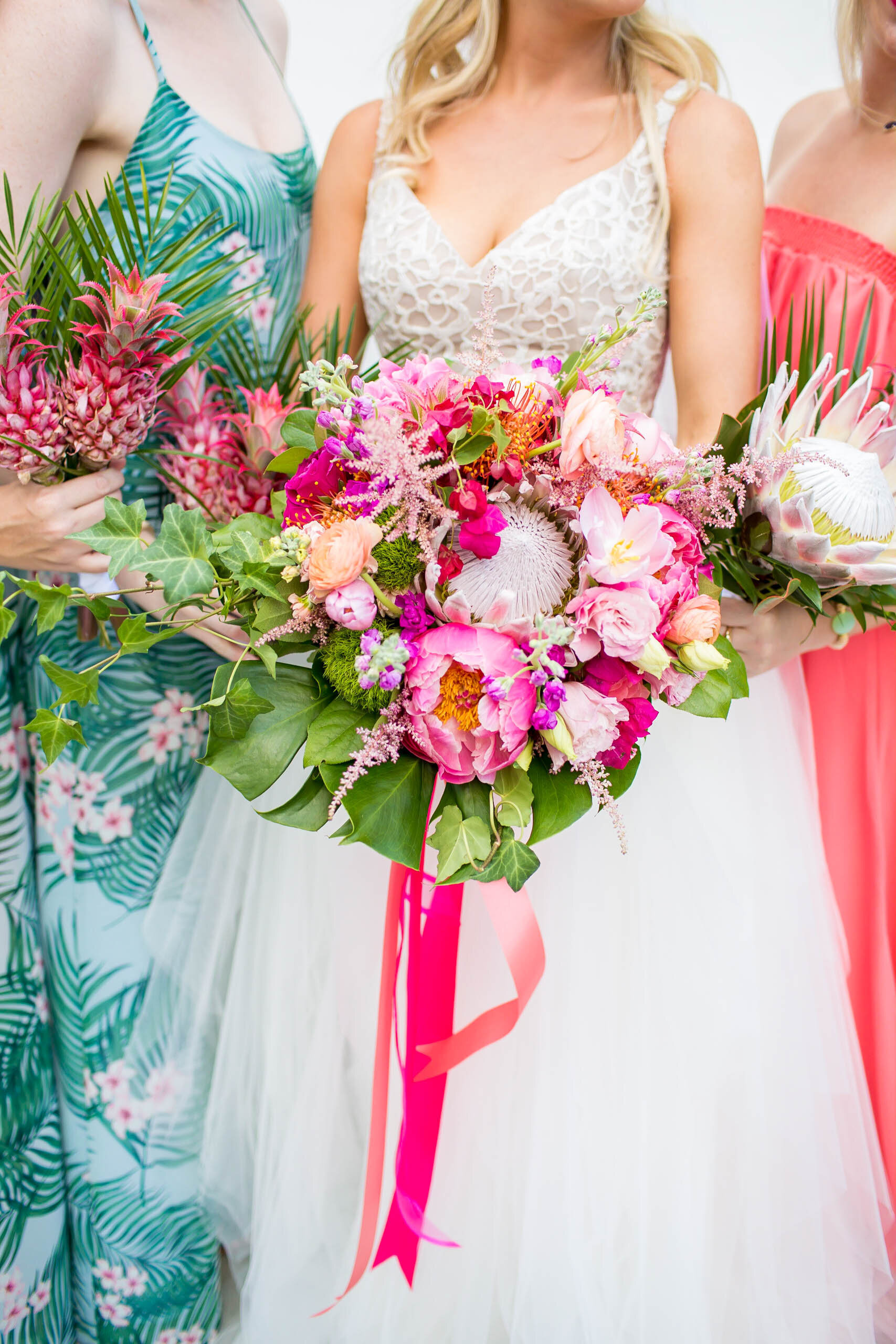 bride and bridesmaids holding colorful flowers