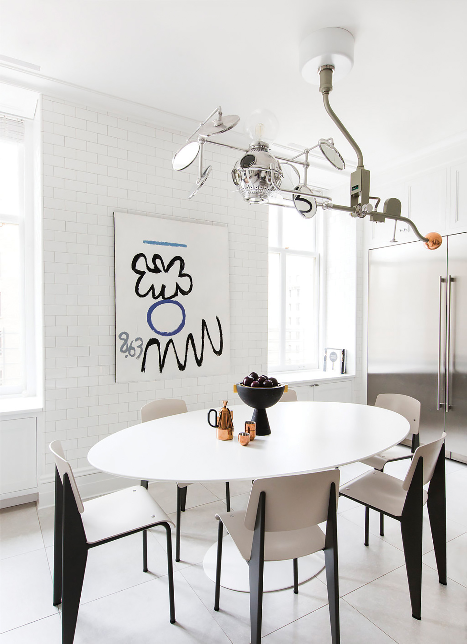 Vintage surgical light over Saarinen oval dining table. Prouve Standard chairs. Artwork by Raymond Hendler. Apparatus Censer dome and Tom Dixon Brew Coffeeware set. Photo: Tessa Neustadt.