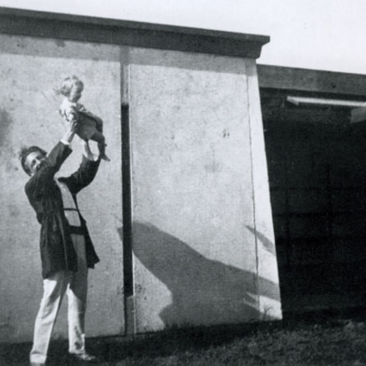 Schindler at his home and studio, the Kings Road House, holding Richard and Dion Neutra's son, Dion. A pinwheel shape to house two families, the Neutras lived at the Kings Road House upon their arrival to LA in the mid 1920s until 1930.